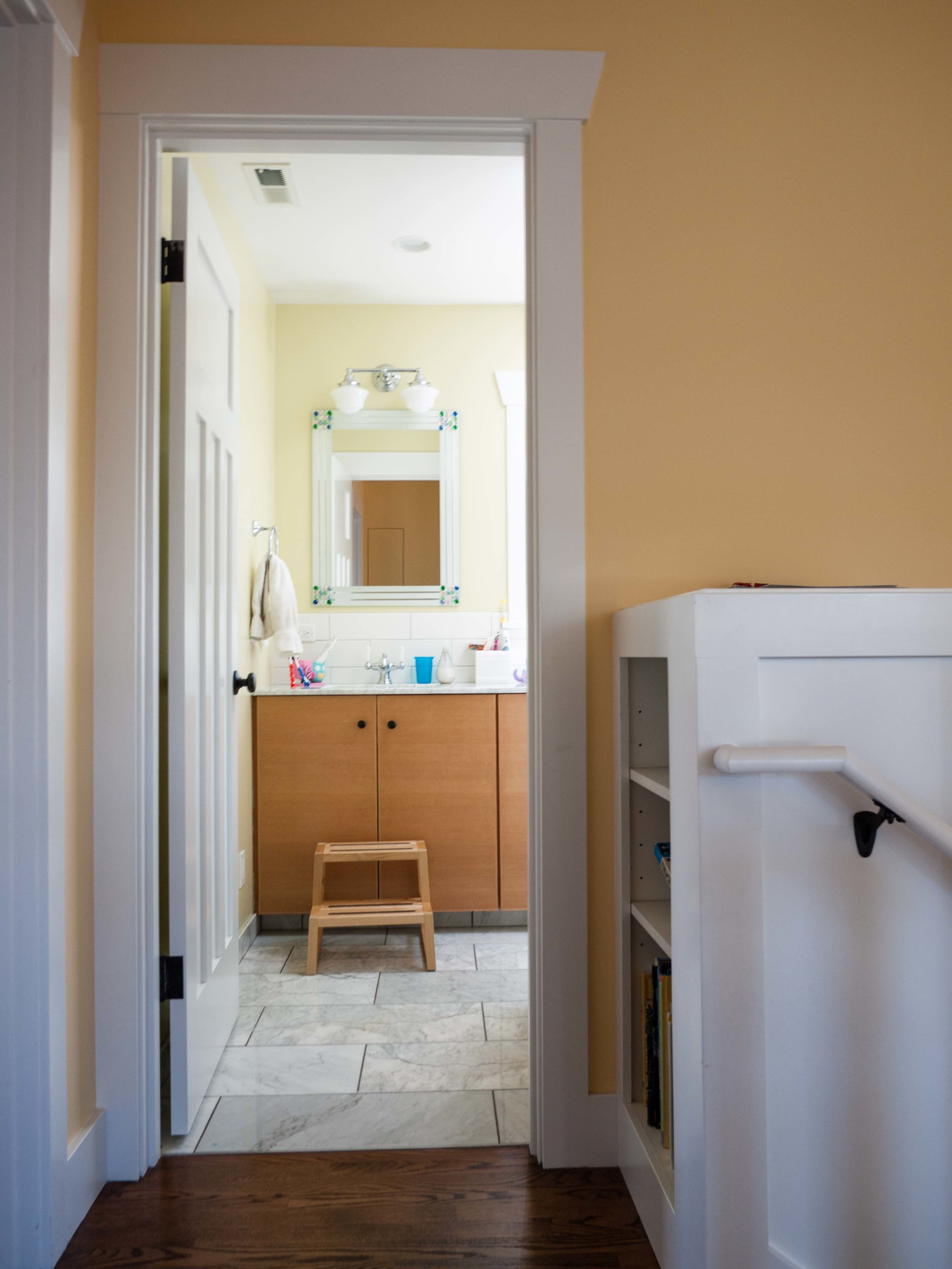 At the top of the stairs and adjacent to the kids' rooms is the kids' bathroom.