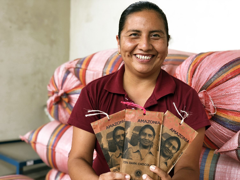 Cocoa farmer Monica Guaman holding (and featured on) the 72% Zamora, Amazonia dark chocolate bar by Askinosie. Photo credit: Askinosie Chocolate