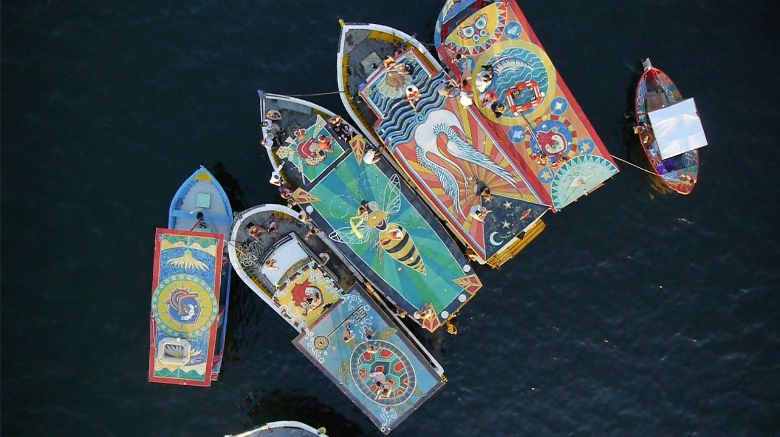 Aerial View of 6 boats at FlutuArte's closing event.    In 2012, Maxine co-created  FlutuArte , a public art installation where 45 international artists joined to paint murals on the rooftops of 60 fishing boats in a historic harbor in Rio de Janeiro, Brazil. FlutuArte brought not only new vibrant colors to this fishing community, but also a new economy of tourism.