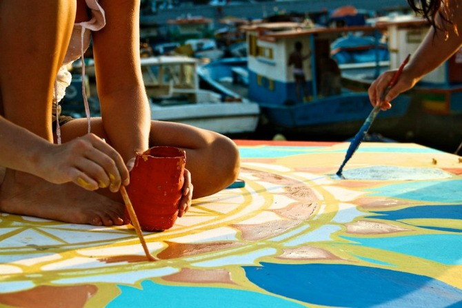 Maxine and co creator  Nicolina  painting a mural on a boat rooftop     In 2012, Maxine co-created  FlutuArte , a public art installation where 45 international artists joined to paint murals on the rooftops of 60 fishing boats in a historic harbor in Rio de Janeiro, Brazil. FlutuArte brought not only new vibrant colors to this fishing community, but also a new economy of tourism.