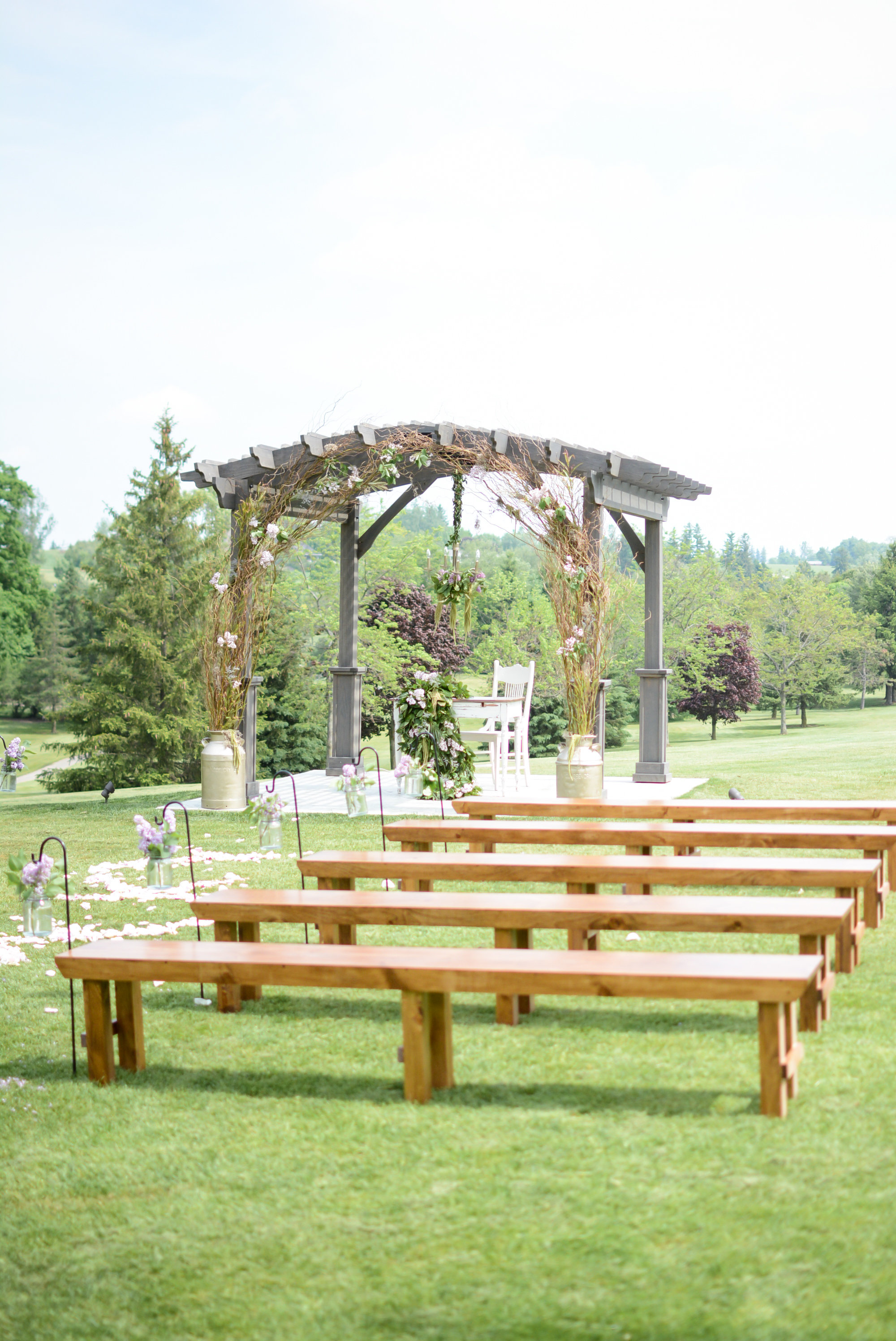 Harvest benches lend an earth-grounded and rustic appeal to the ceremony setting at St. Marys. Photography:    Nina Polidoro   . Decor & Styling:    Above & Beyond Event Design   . Floral Design:    Lyric Flowers   .