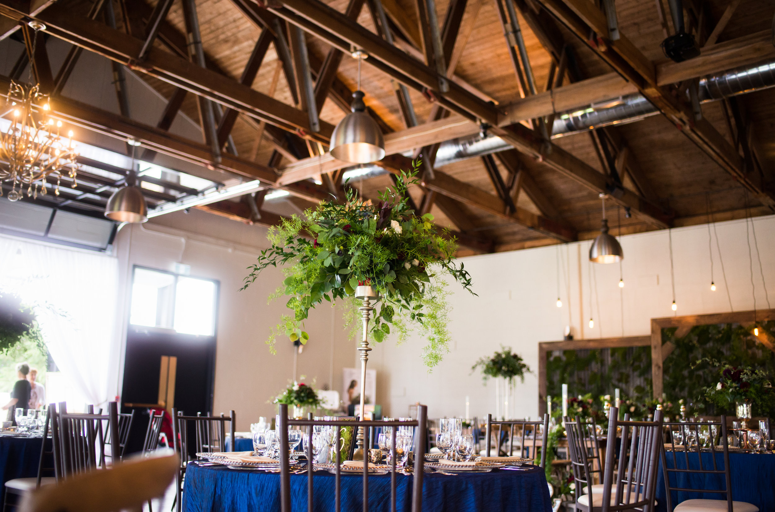 The Hideaway  reception space features an exposed wood beam ceiling, elegant chandeliers and pendant lighting, dark-framed Chiavari chairs, and massive black-pane garage doors.