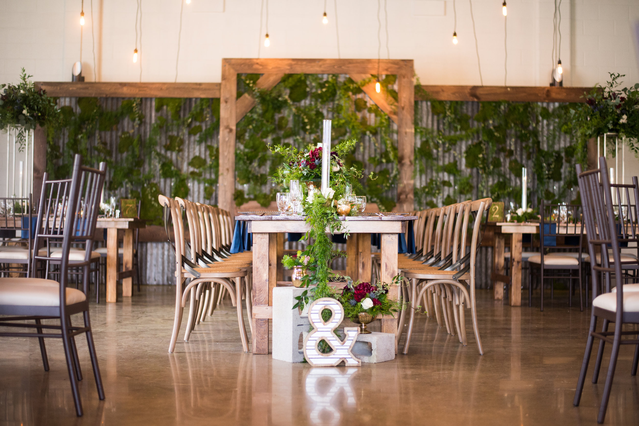 Wood harvest tables and vineyard chairs are always a beautiful choice for a Head Table, especially when they're setup king's style and feature a greenery garland. Venue:  St. Marys Golf & Country Club . Decor & Styling:  Above & Beyond Event Design . Floral Design:  Lyric Flowers .