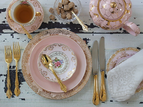 Vintage place settings and family heirlooms make for beautiful decor at a tea party-themed bridal shower.