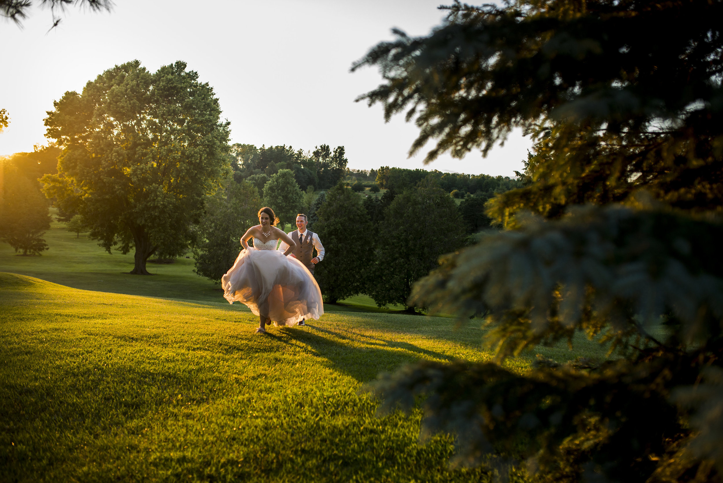 The bride playfully being chased by her groom during sunset makes for perfect candid shots. Photography:    Jen Linfield   .