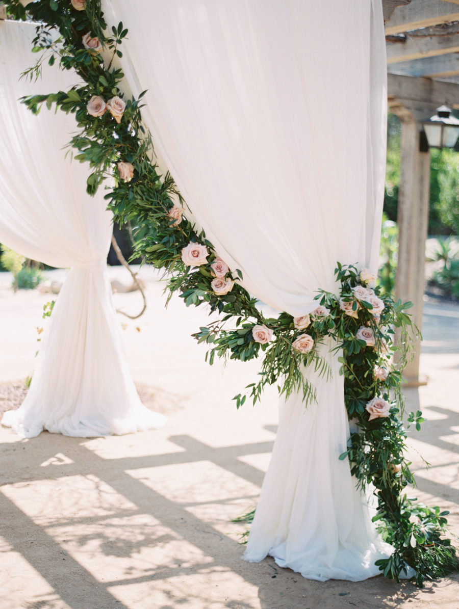 Reception entrances dressed in flowing drapery, greenery and floral make a major statement right when guests enter the space. Photo Source:    Style Me Pretty   .