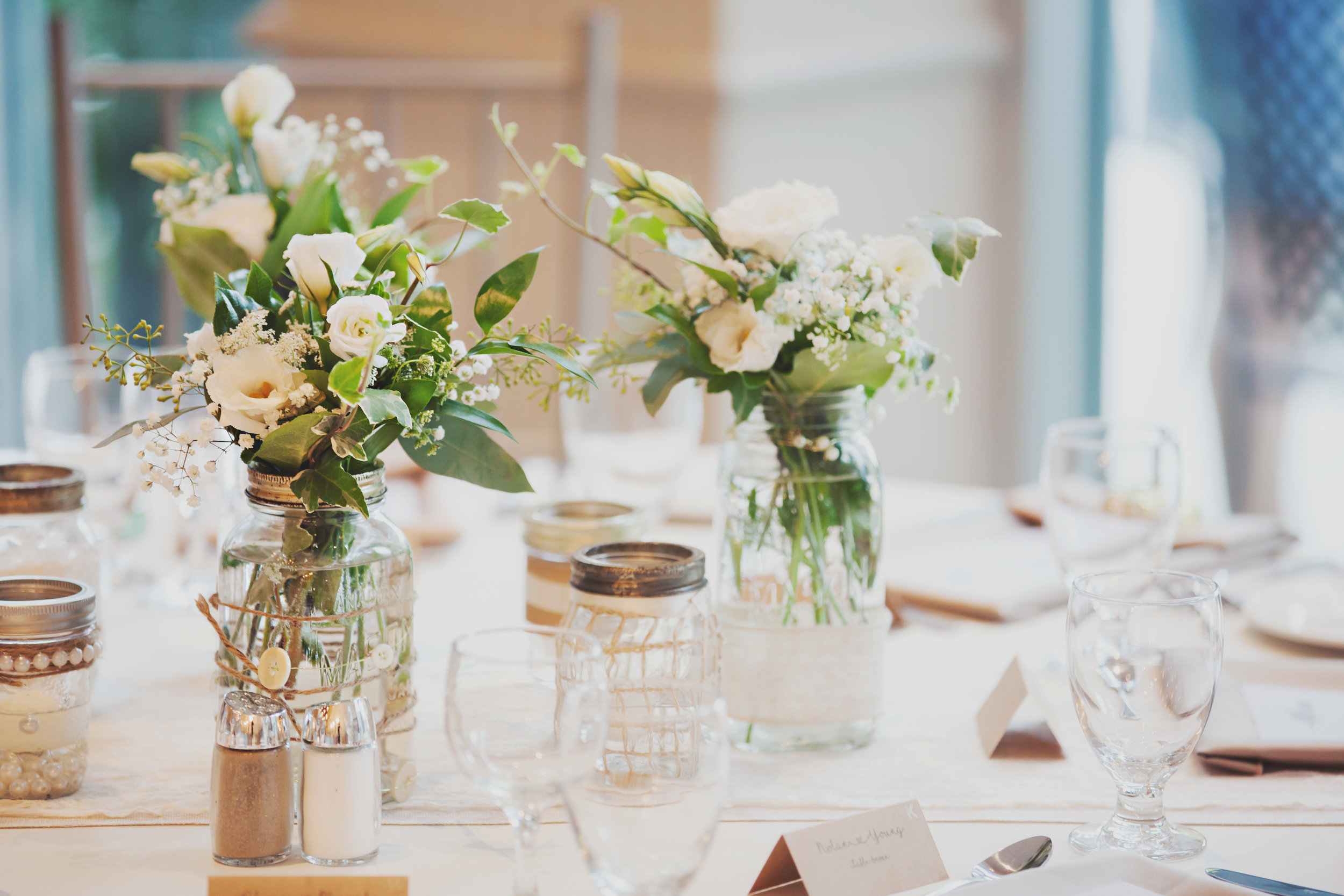Greenery and floral displayed in varying mason jars provides an organic, artistic, and garden-inspired vibe to a    Ballroom    reception. Floral Design:    Lyric Flowers   .