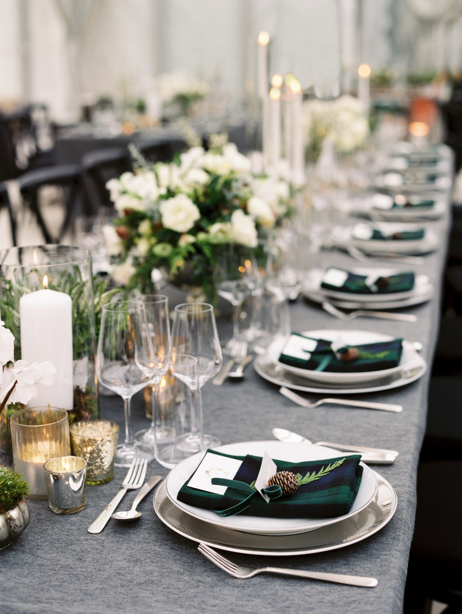 Plaid napkins adorned with forest green velvet bows and sprigs of spine add holiday cheer to a winter wedding place setting. Photo Source:  Style Me Pretty .