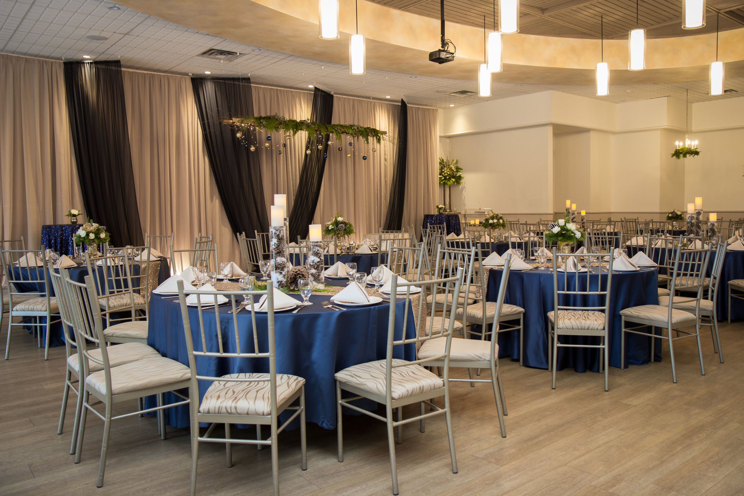 Rich navy blue linen, suspended winter greens, and flickering candlelight add an intimate holiday feel to a winter wedding setup. Venue:  St. Marys Golf & Country Club . Decor & Styling:  Above & Beyond Event Design . Floral Design:  Lyric Flowers . Photography: David Jordan Photography.