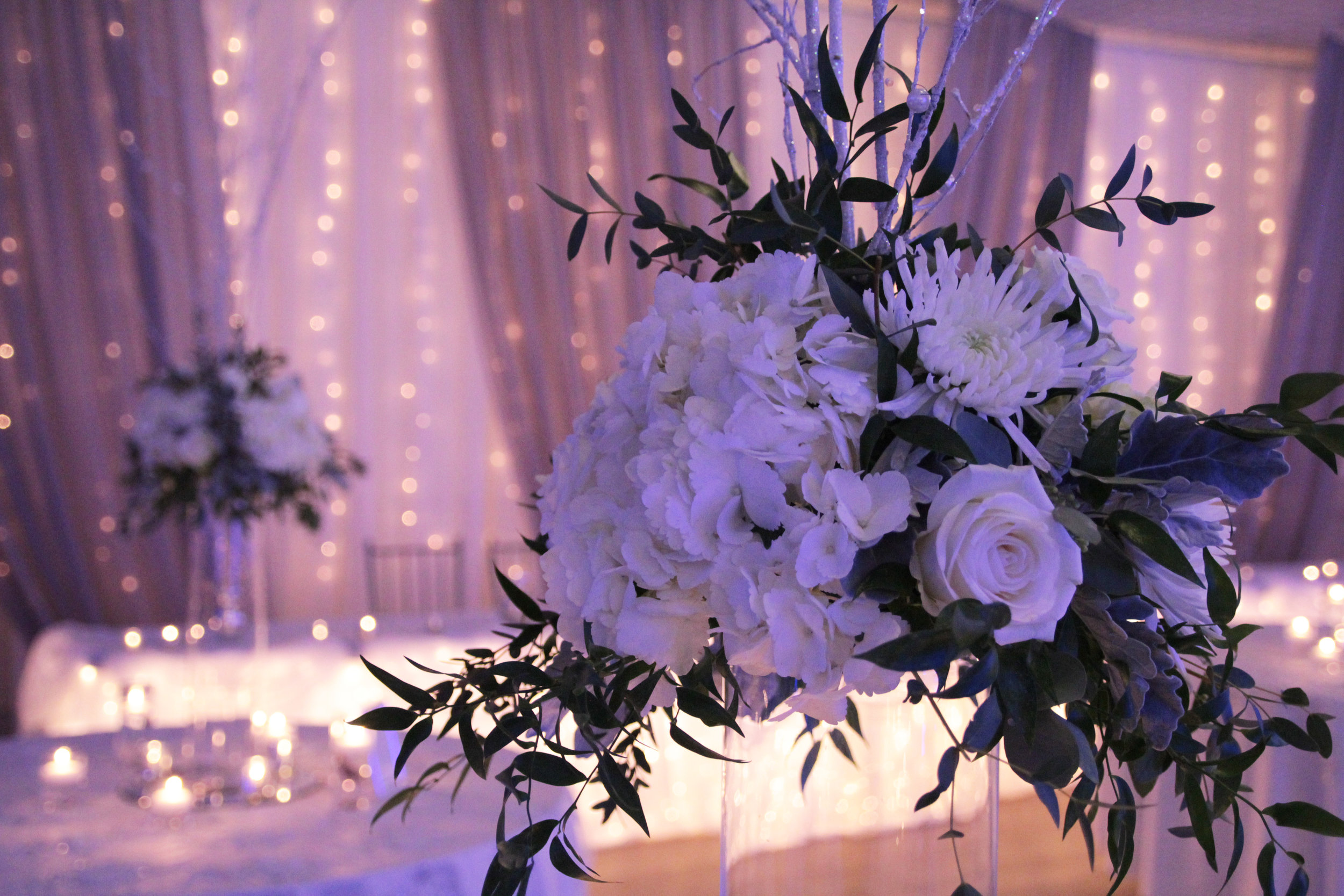Flower arrangements done in monochromatic colour schemes of all white look elegant, glamourous, and timeless for a black tie winter wedding affair.