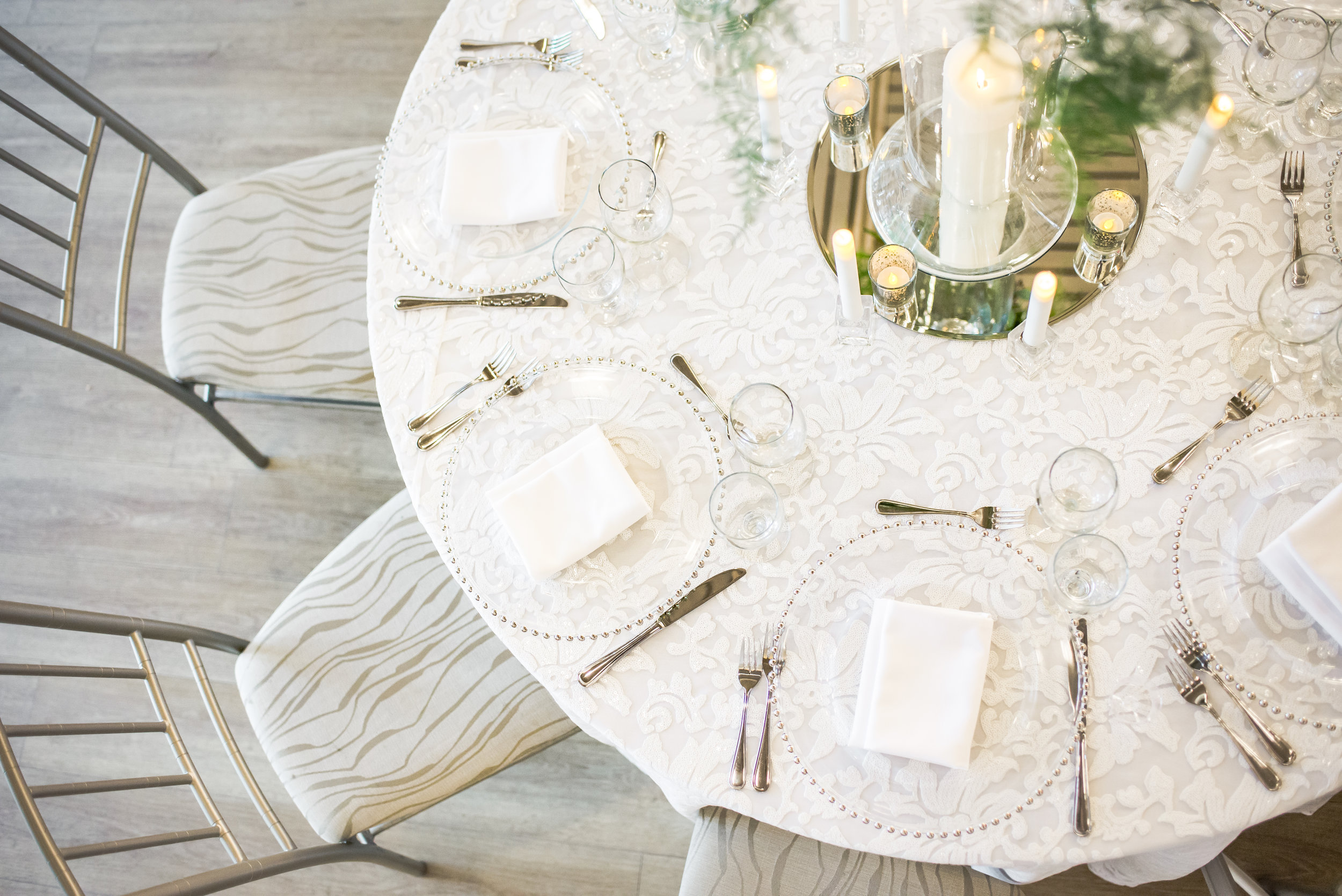 Guest table displays in the Ballroom were just as beautiful as the king's table, dressed with coordinating lace-embroidered linen, glass and mirrored details, and loads of candlelight.