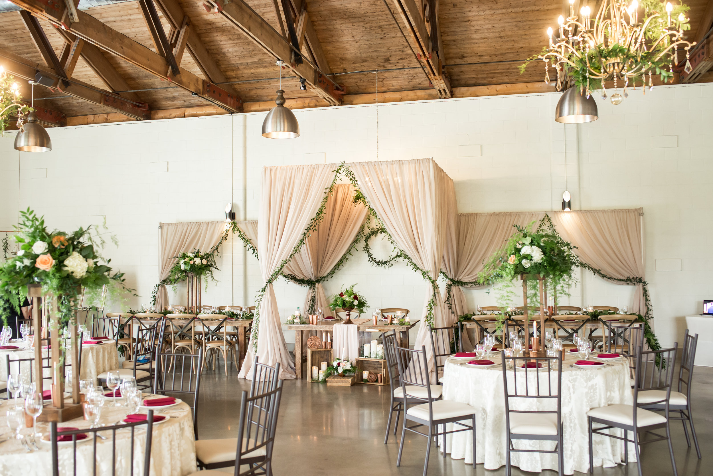 Inspired by a secret garden theme, the Hideaway design included details that were at the same time polished and undone. A stunning draped chuppah, greenery accents and bursts of floral everywhere, and wood tables and chairs elevated the space perfectly.