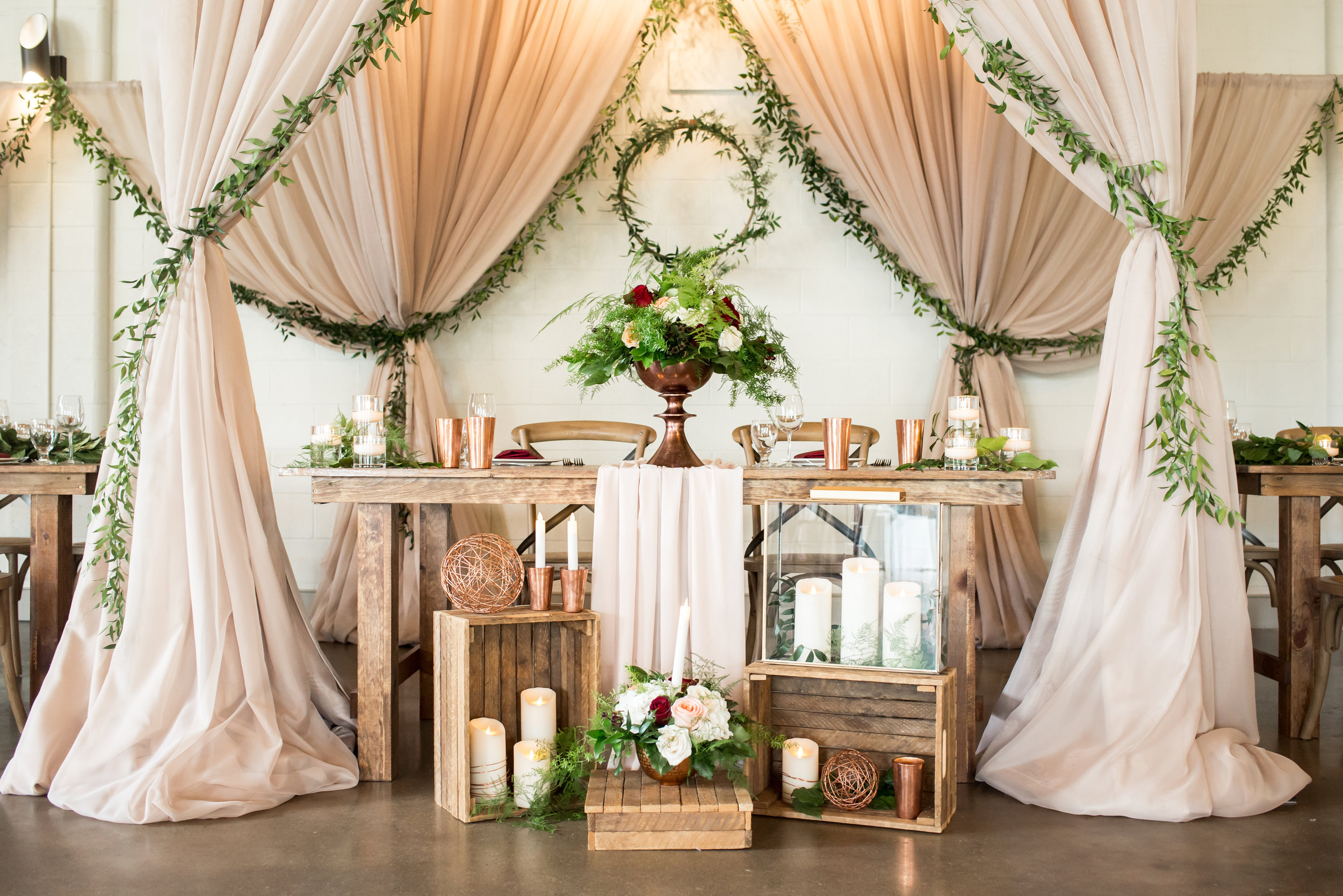 An intimate sweetheart table was set beneath the chuppah at the center of the Hideaway design, with romantic accents like a flowing chiffon runner, greenery wreath and garland, and a multitude of candlelight.