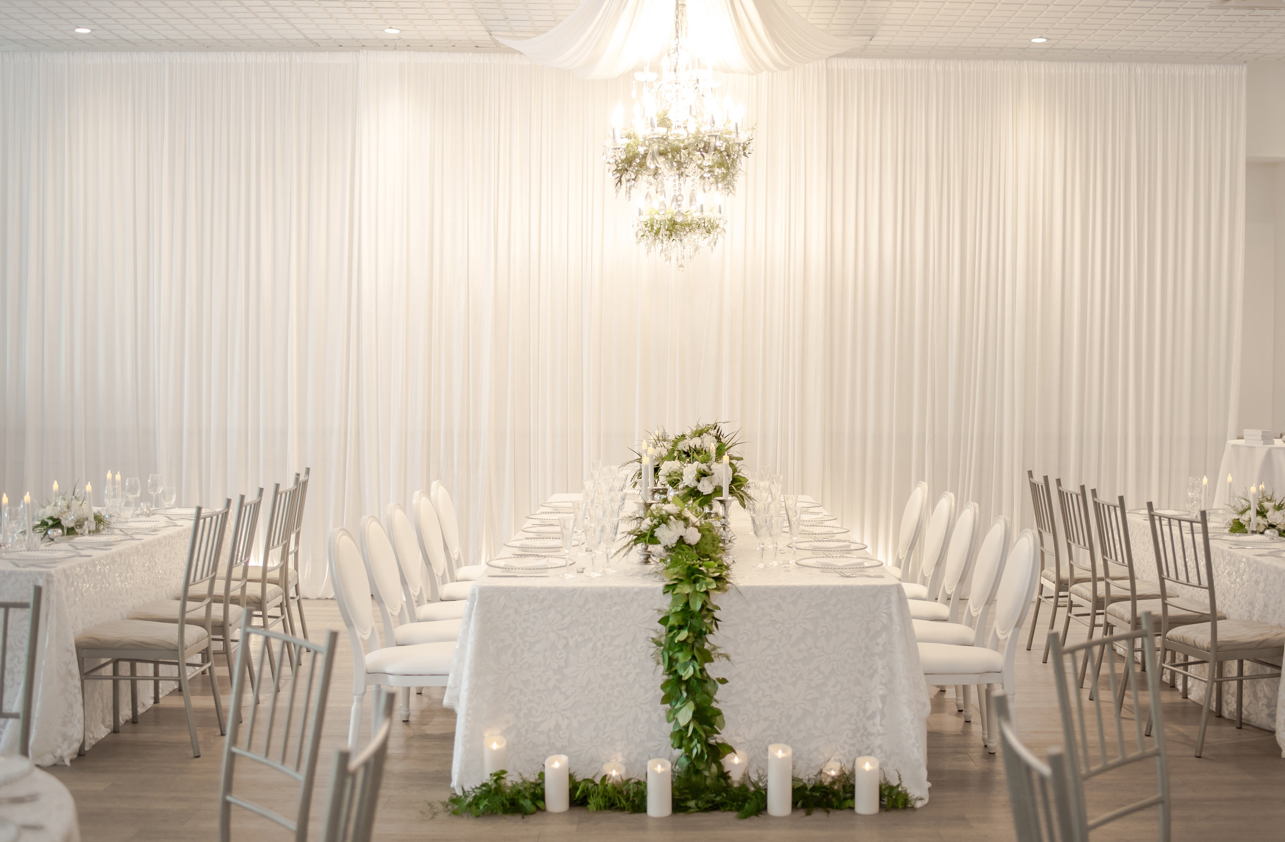 Set against a flowing white backdrop, the elaborate king's table display in the Ballroom included everything from a lush greenery runner, crystal chandeliers and stemware, to the ever-classic white Louis XVI dining chair.