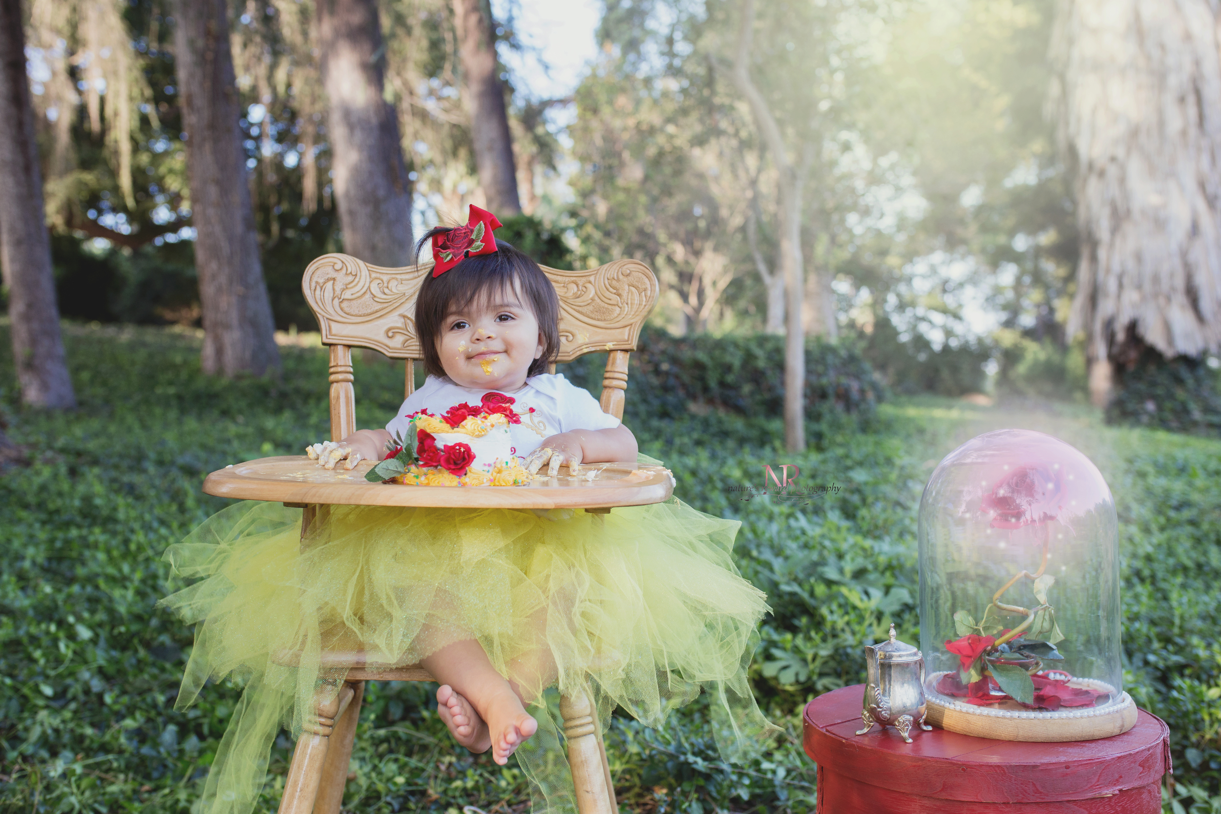 This Beauti ful Belle grinning as she is covered in yellow and white frosting with her enchanted rose in this Disney's Beauty and the Beast Inspired cake smash session in redlands, california.