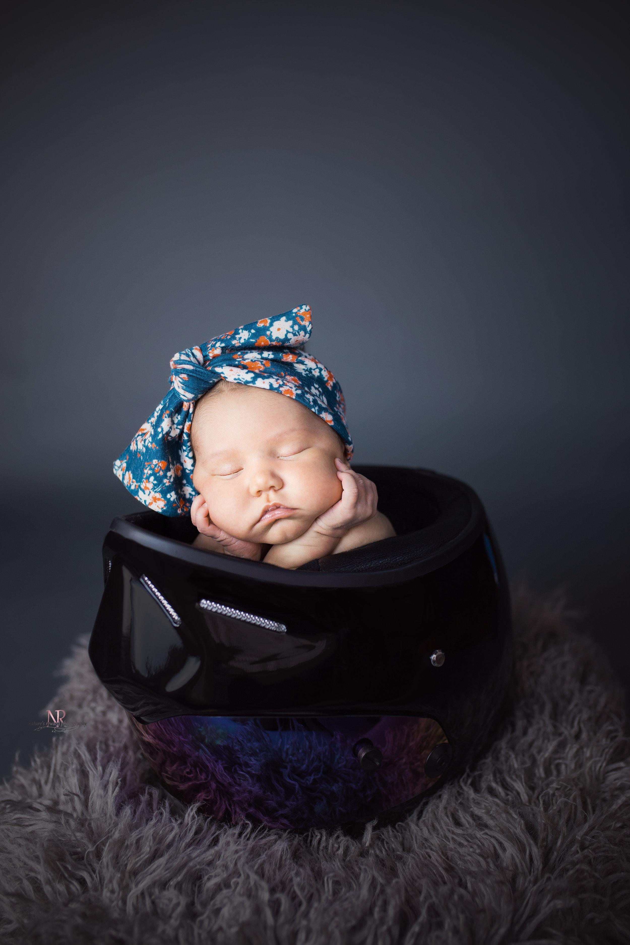 Newborn portrait in color of baby girl in her dad's motorcycle helmet taken by Nature's Reward Photography