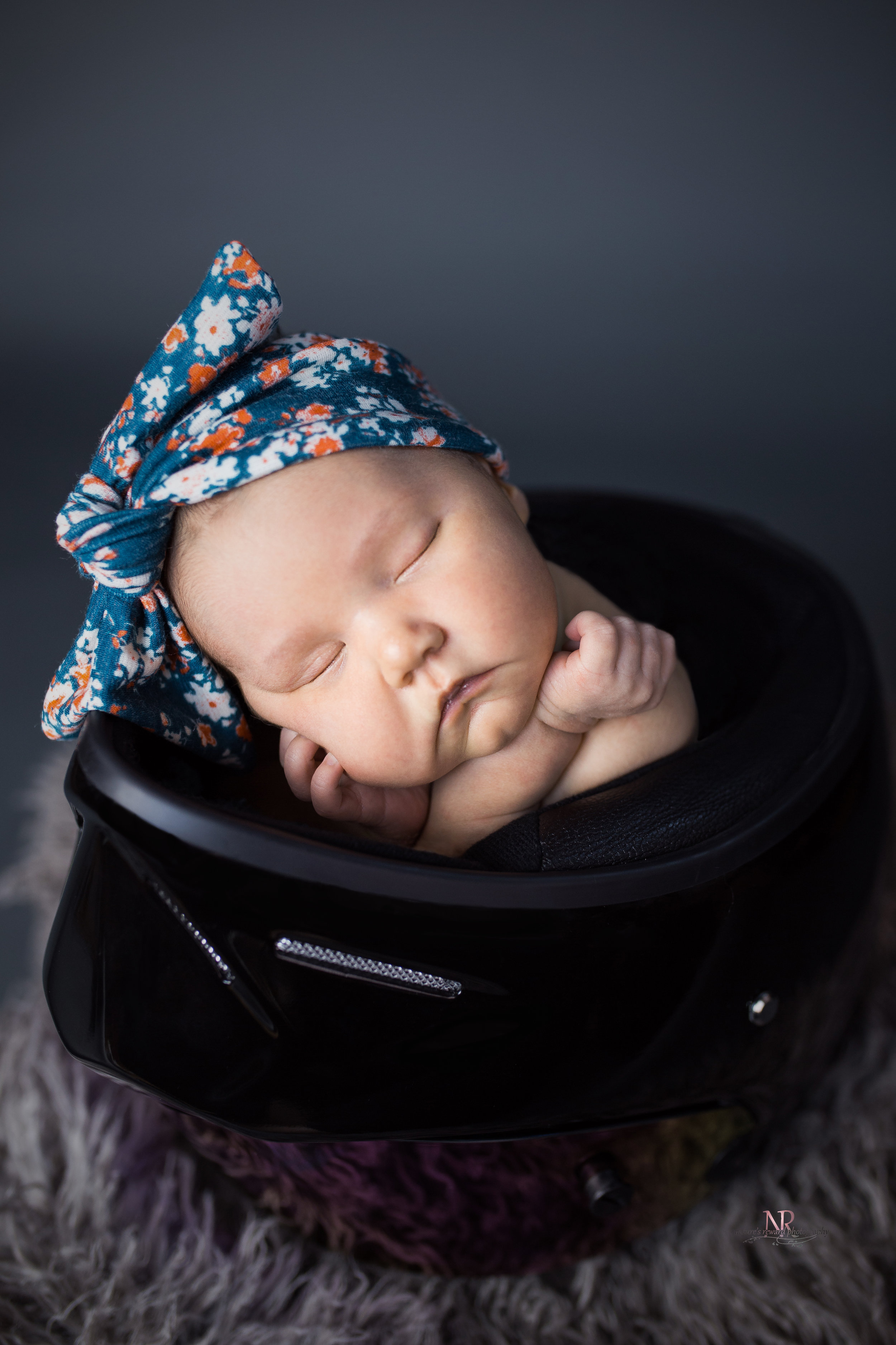 Newborn close up portrait in color of baby girl in her dad's motorcycle helmet taken by Nature's Reward Photography