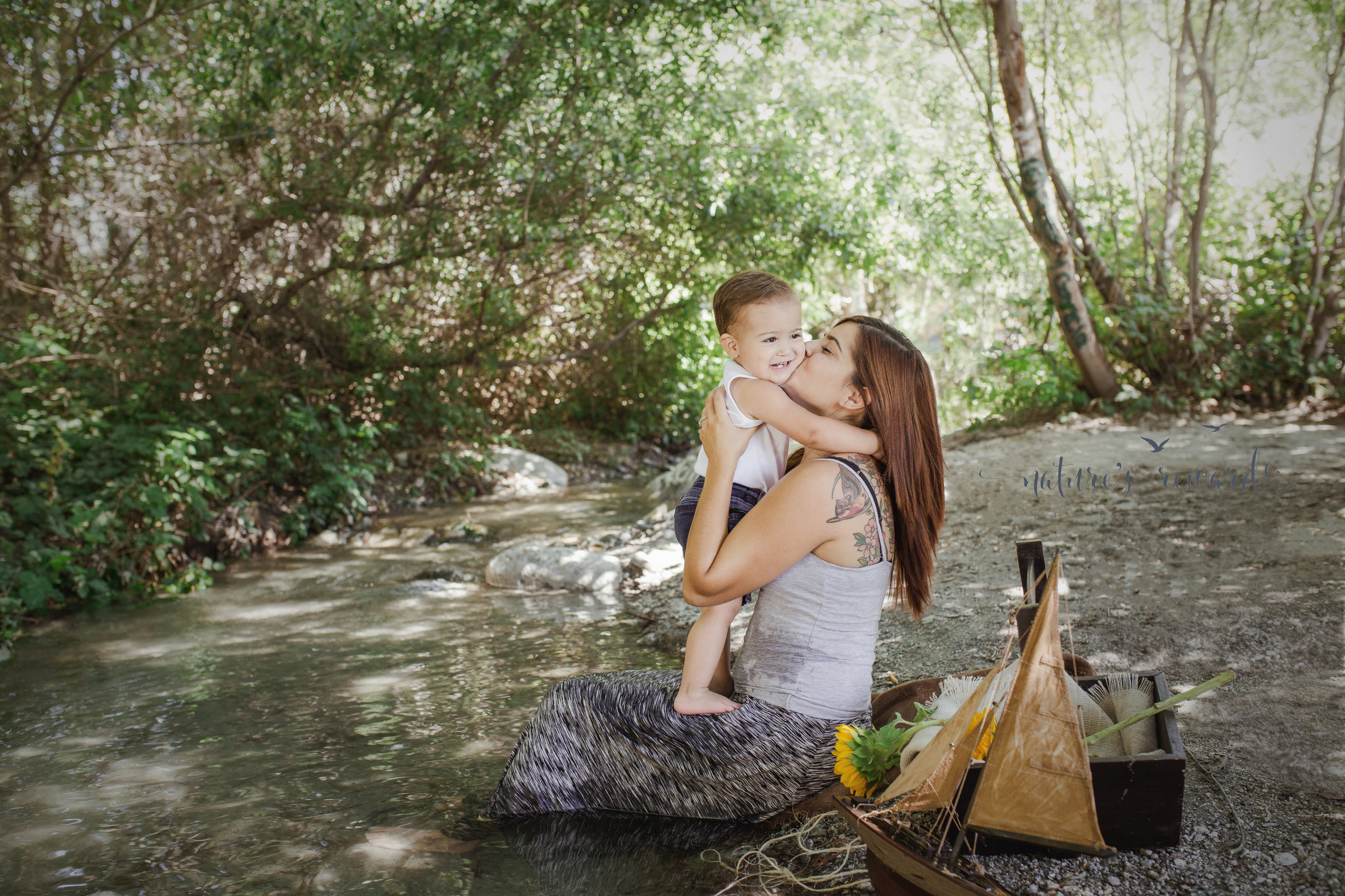 He hugged her and smiled with joy in this mother and son creekside portrai. Image by Nature's Reward Photography, a Southern California newborn, family and child photographer