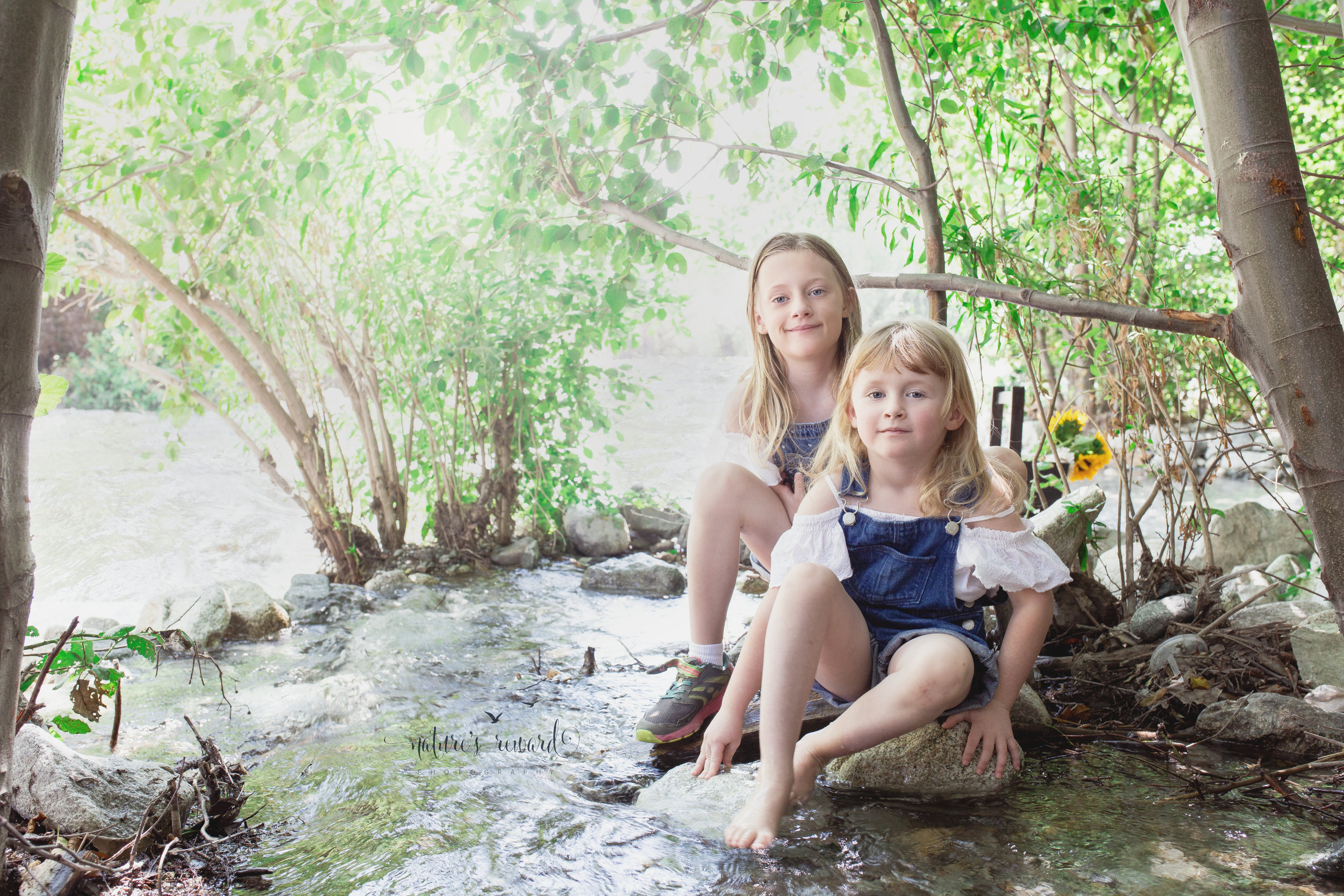 These lovely girls sitting on the rocks while the stream rolls by. Portrait by Nature's Reward Photography- a southern California photographer