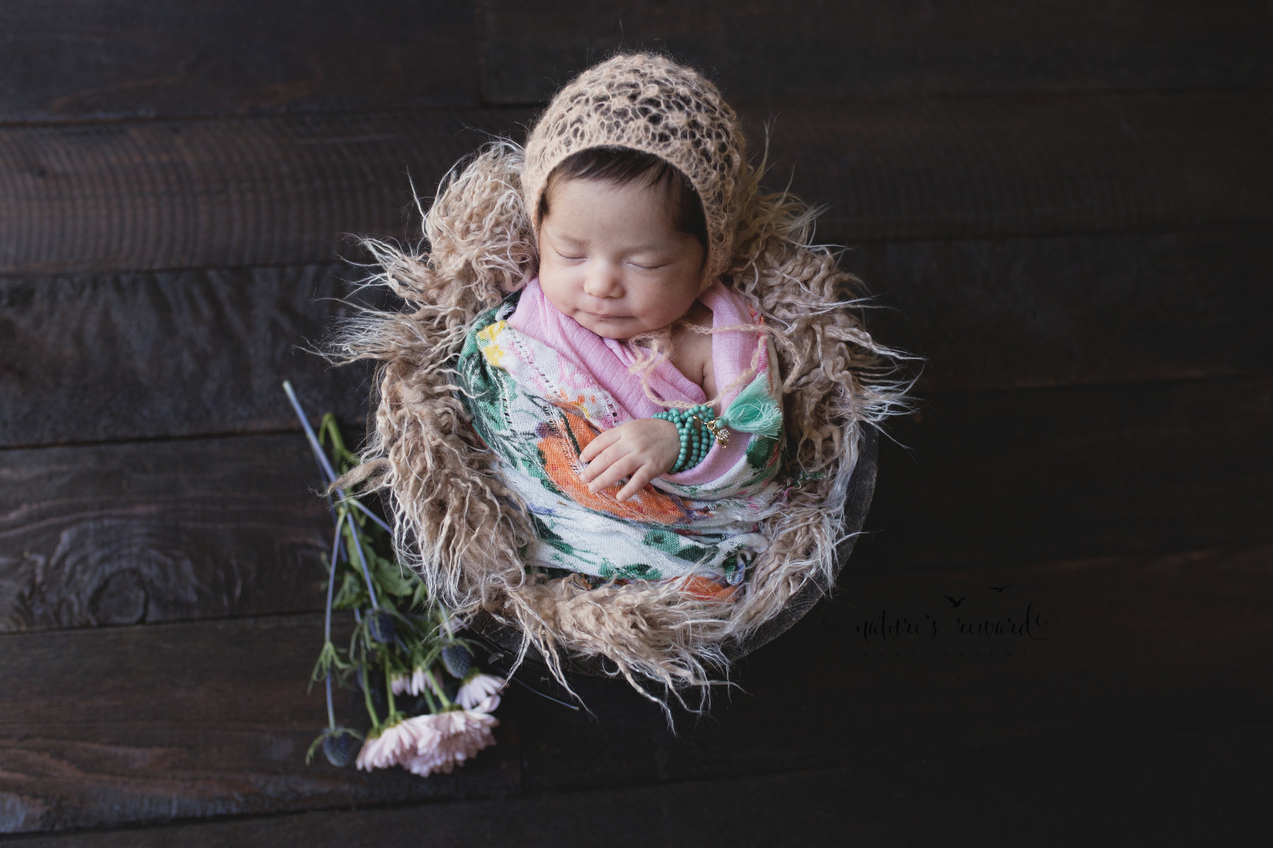 I added the wrap that her mother was in love with. Then we placed this lovely coral bonnet by The Crafty European, and a little doodad bracelet to make this baby in bucket complete Image by Nature's Reward Photography