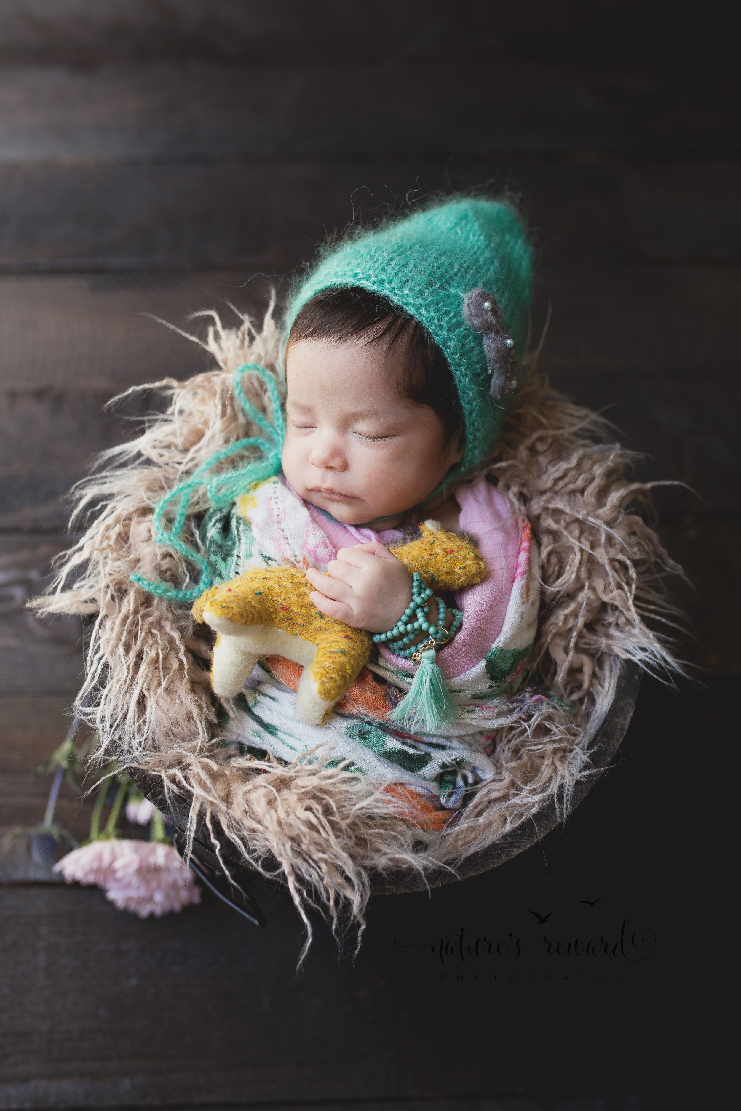 Can we just take a moment and adore this image! The bonnet by The Crafty European pops among the wrap and the bracelet in this newborn baby girl image in a bucket in natural window light with her baby giraffe popping yellow! GAH!Image by Nature's Reward Photography