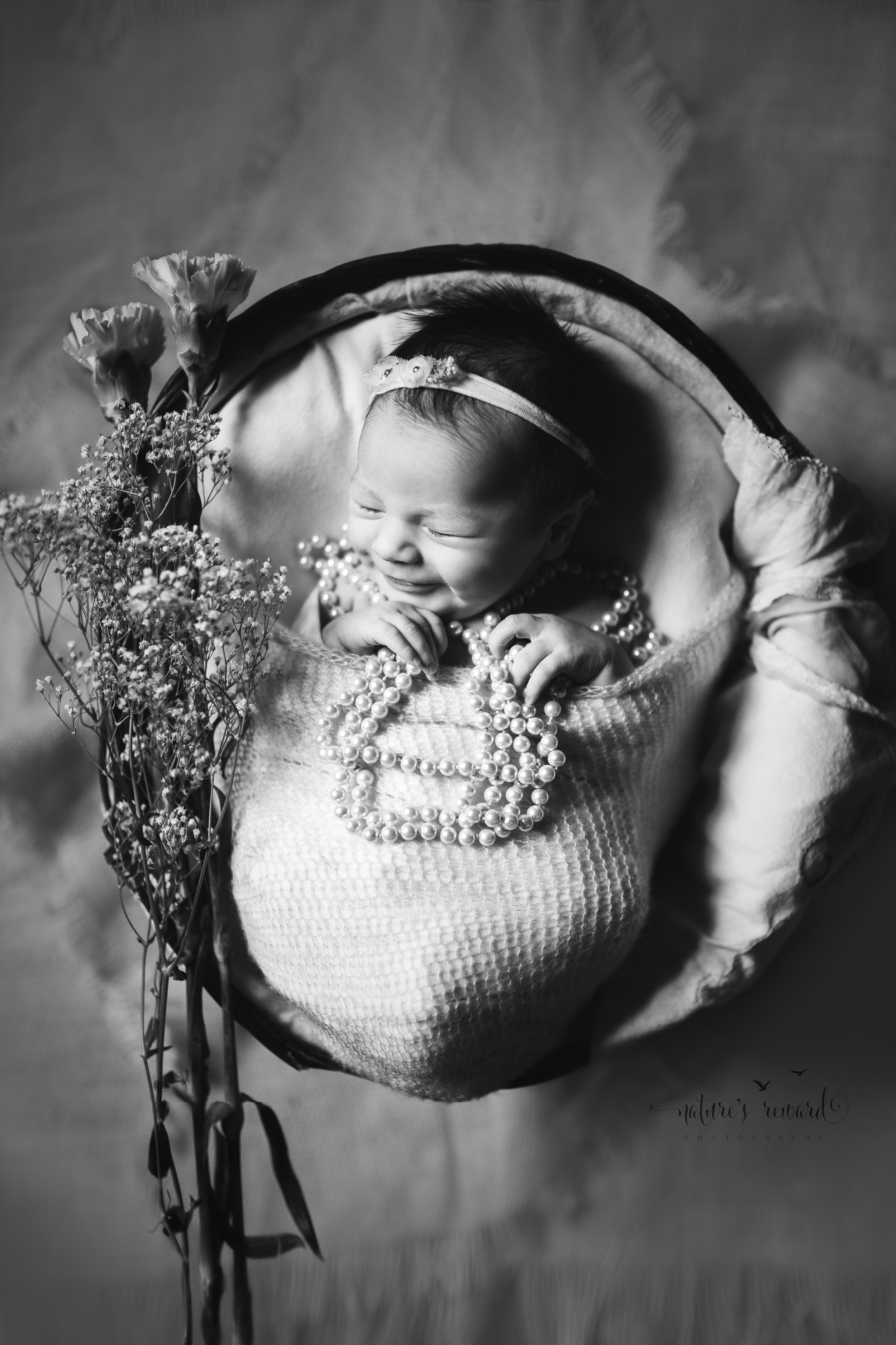 And this black and white makes her smile pop off the page!  This newborn girl in pearls and adorned in flowers and showing off a contagious smile!