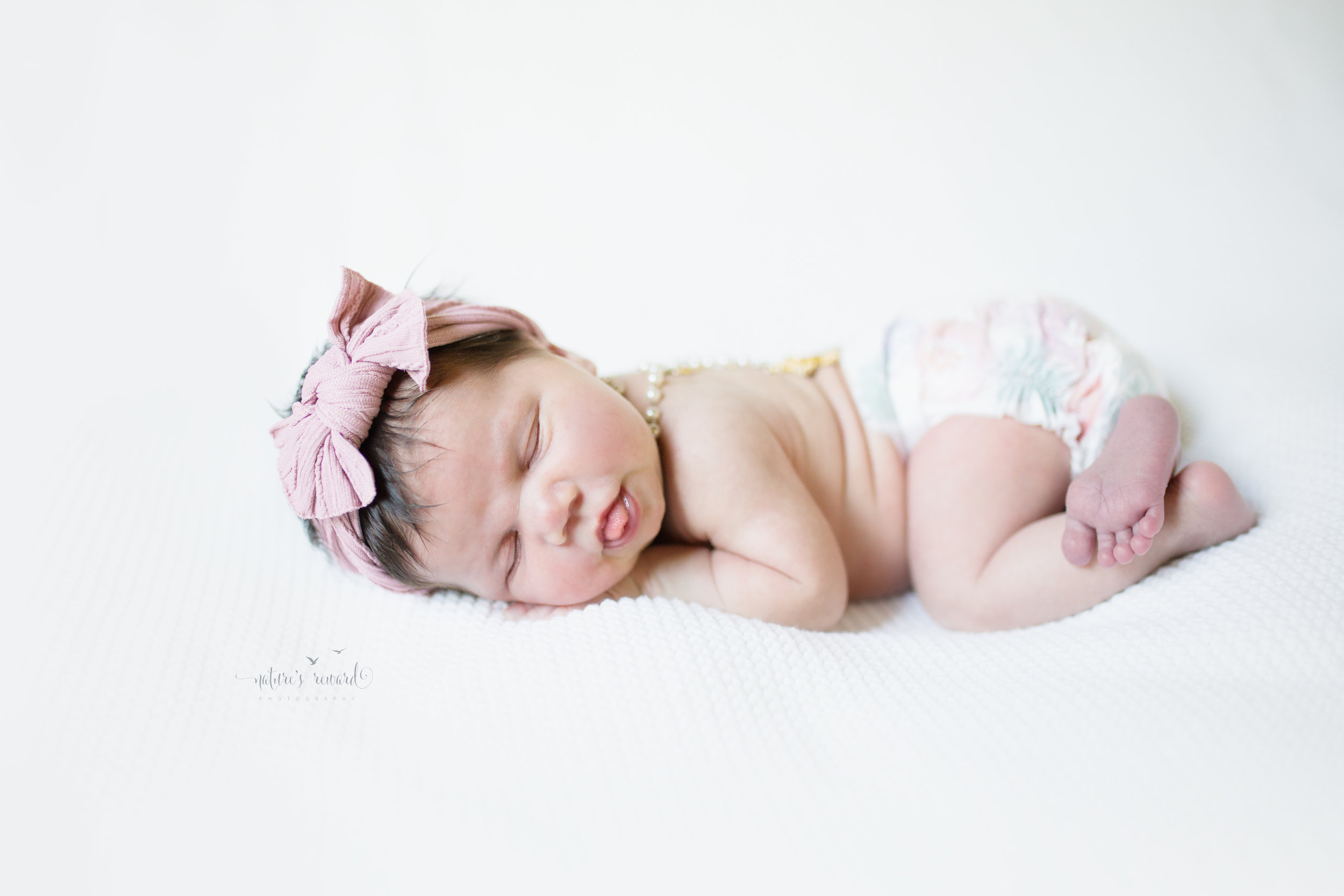 Beautiful baby. Her rosary along her back in a flower diaper and pink headband. Perfection, as she cues us it is time to eat.