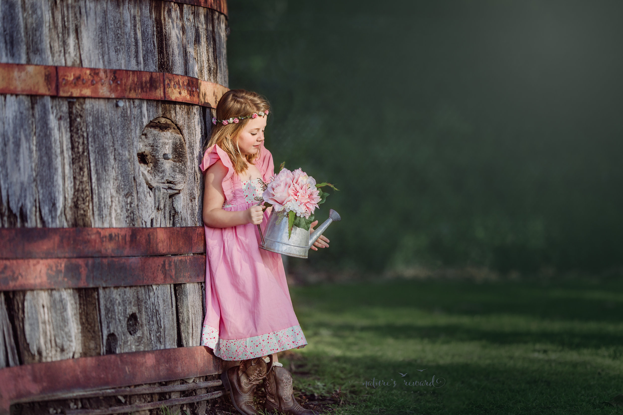 Sweet child in a pink dress holding a watering can and flowers in this nostalgic portrait by Nature's Reward Photography, a Southern California Photographer