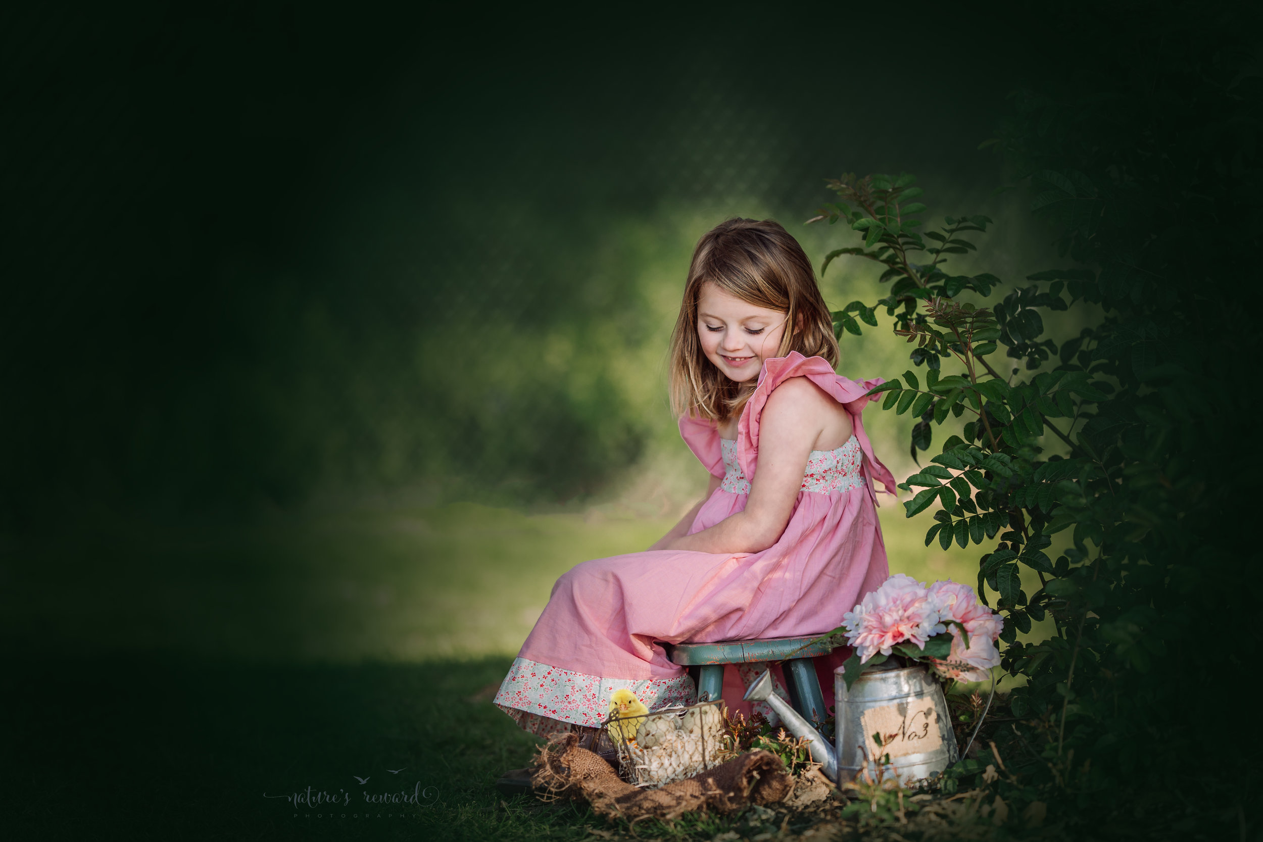 This sweet forever portrait with this lovely girl wearing a pink prairie dress and cowgirl boots while looking down upon a basket of eggs and a composited chick by Nature's Reward Photography, a Southern California Photographer