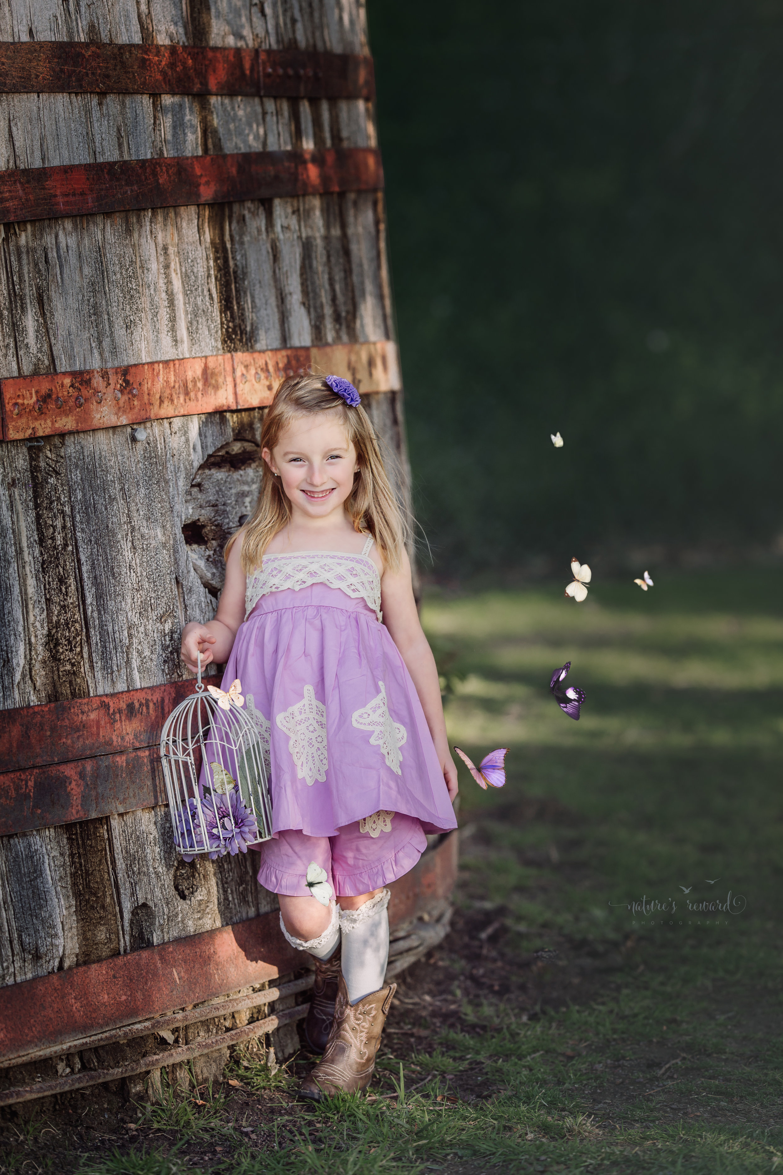 Butterfree in a purple dress and long stockings and cowgirl boots with a bird cage containing purple flowers and a butterfly while butterflies flutter around her in the composite piece by Nature's Reward Photography, a Southern California Photographer