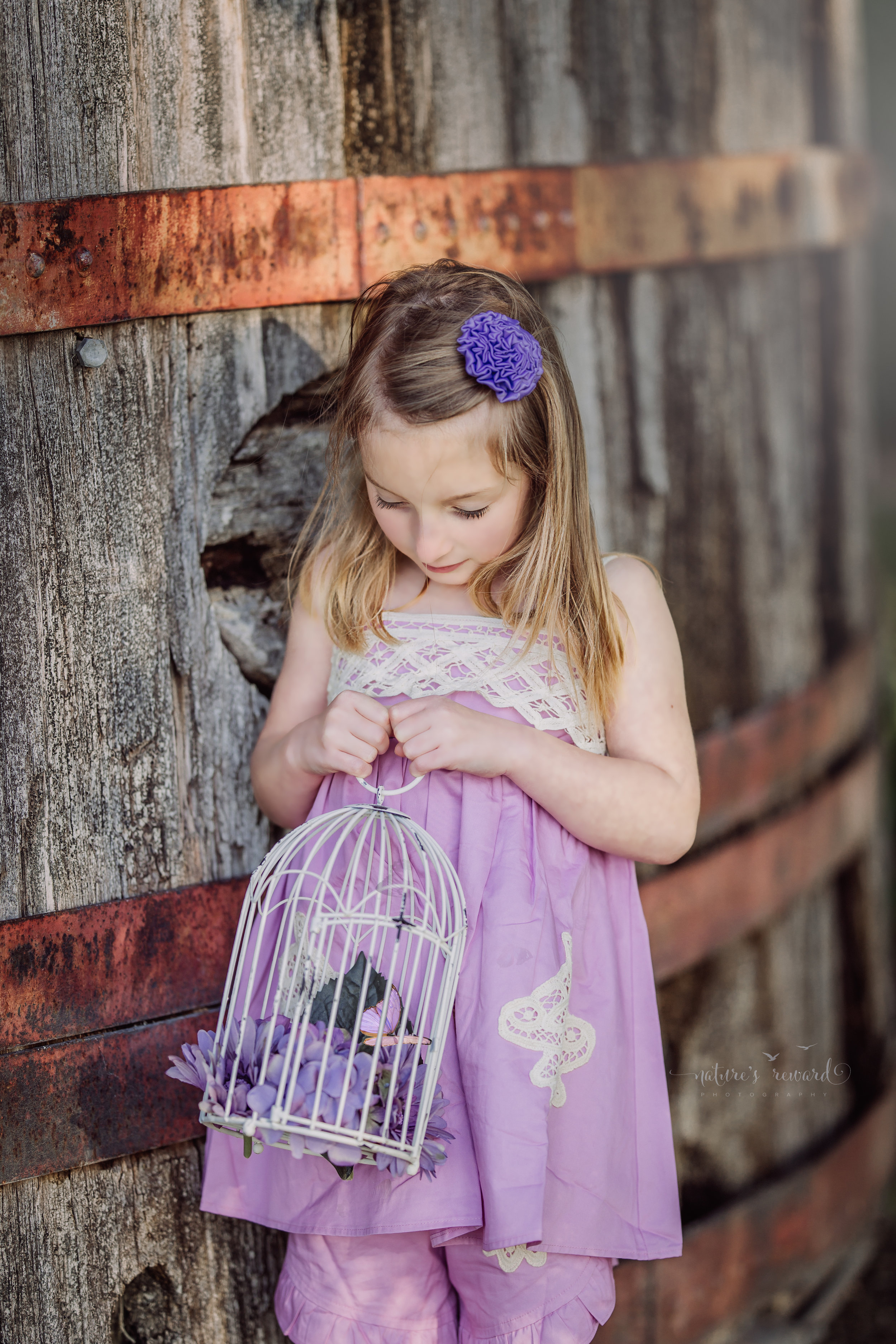Innocence captured in this piece with a purple dress and bloomers holding a bird cage with purple flowers and and a composited butterfly by Nature's Reward Photography, a Southern California Photographer