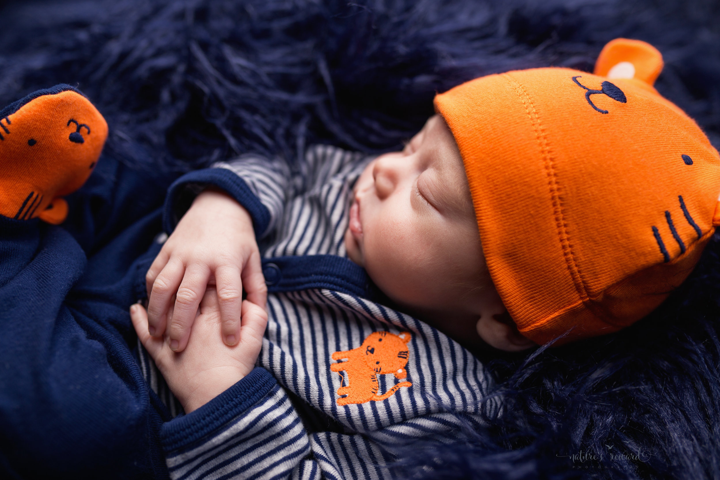 Newborn baby boy wearing an outfit from home showing off his beanie and footsies and his small delicate hands by Southern California newborn and family photographer Nature's Reward Photography