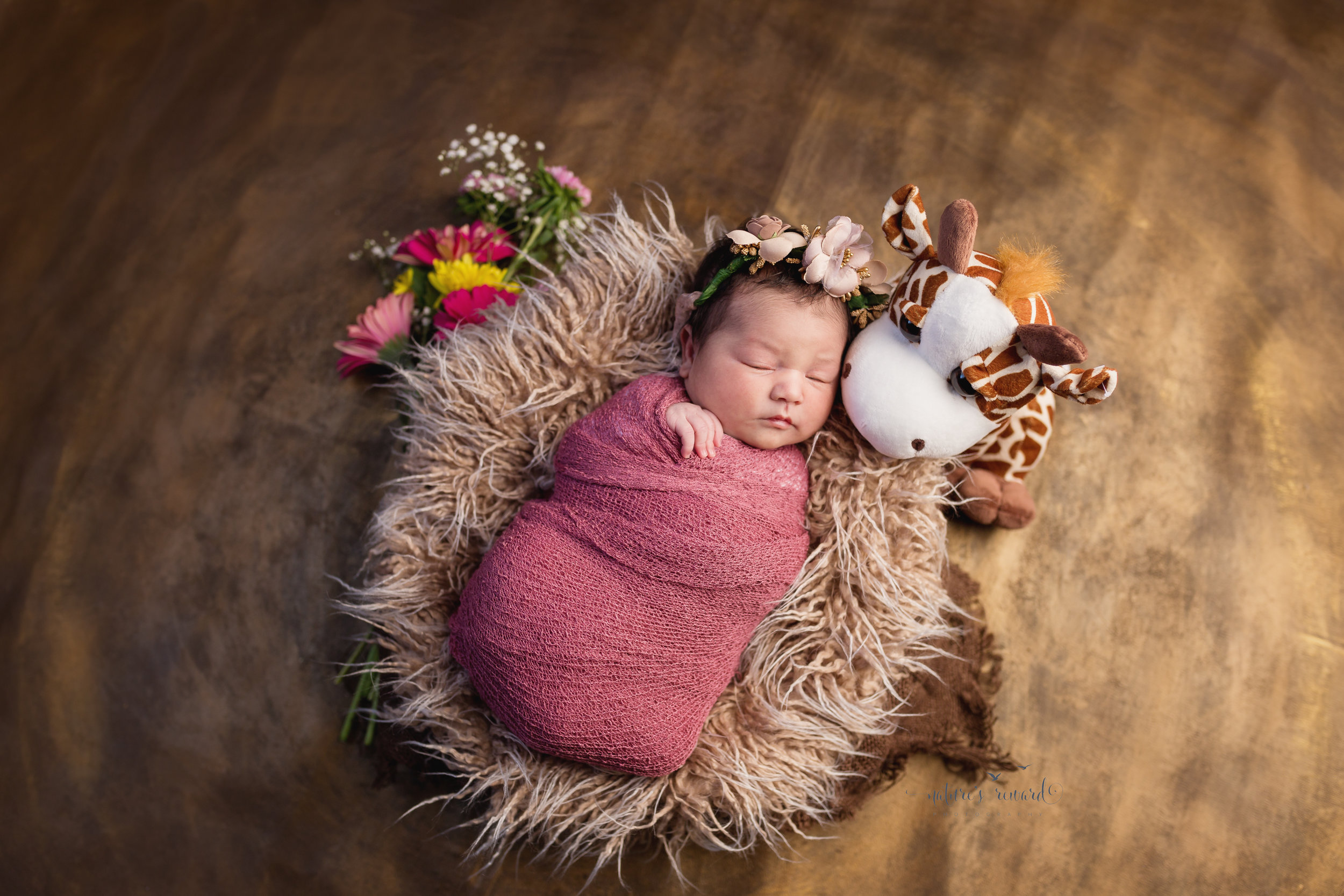 Her sweet giraffe stands watch as she naps swaddled in rose pink on a bed of fur laying on gold accented by flowers and burlap and a sweet blush flower crown by Southern California Newborn and Family Photographer Nature's Reward Photography
