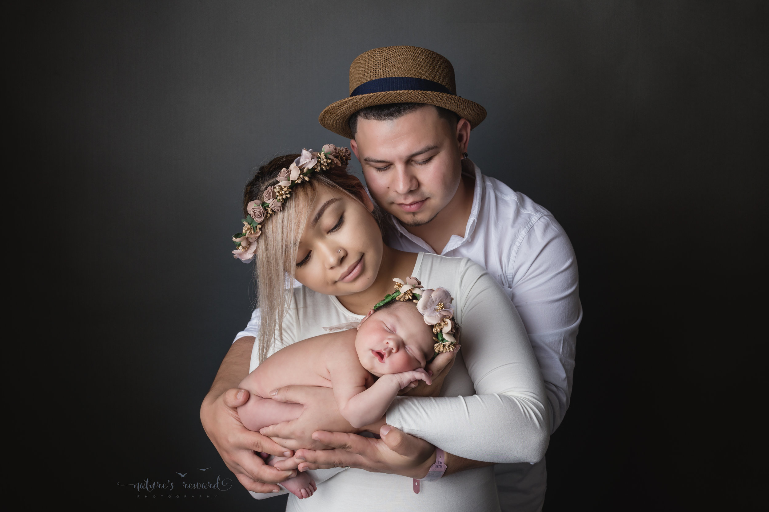 Their family is complete in the warm, white and grey portrait of a family with their newborn baby girl in a flower crown family portrait by Southern California Newborn and Family Photographer Nature's Reward Photography