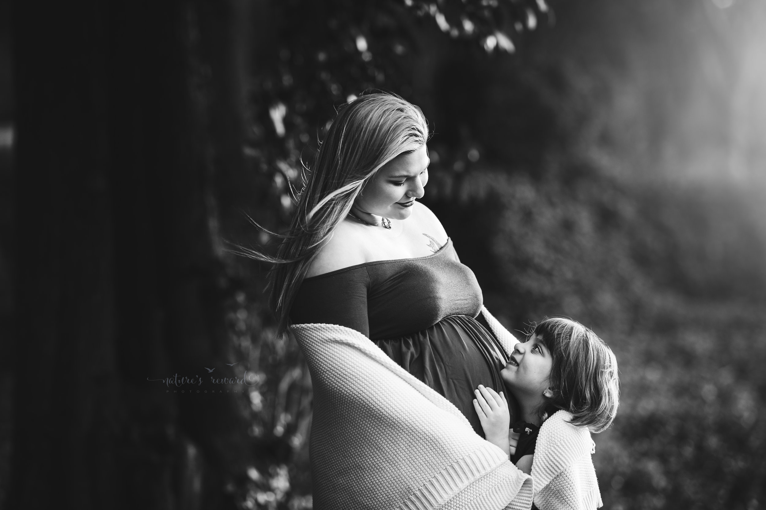 Black and white Maternity portrait of this beautiful expecting mother in a open front purple maternity gown and a beautiful lush park with cherry blossoms and her daughter in this portrait by San Bernardino based photographer Nature's Reward Photography.