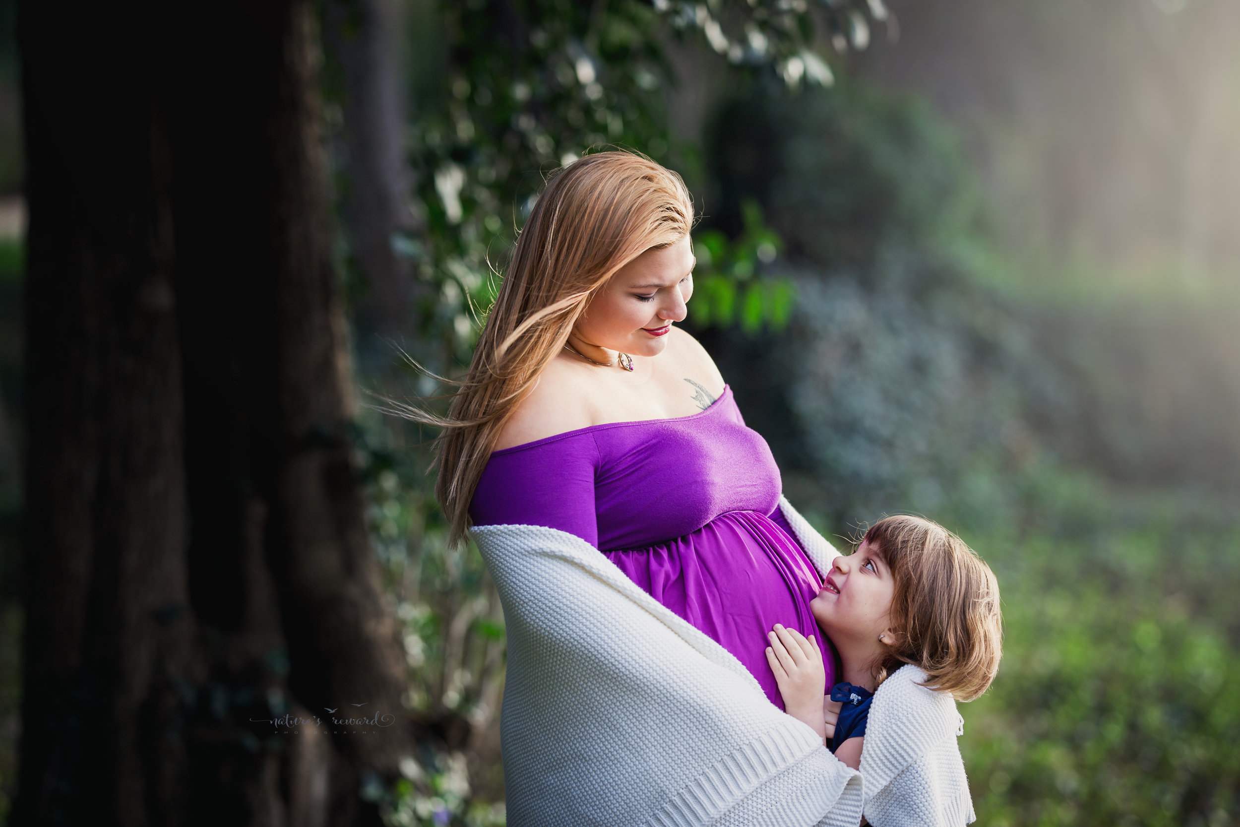 Maternity portrait of this beautiful expecting mother in a open front purple maternity gown and a beautiful lush park with cherry blossoms and her daughter in this portrait by San Bernardino based photographer Nature's Reward Photography.