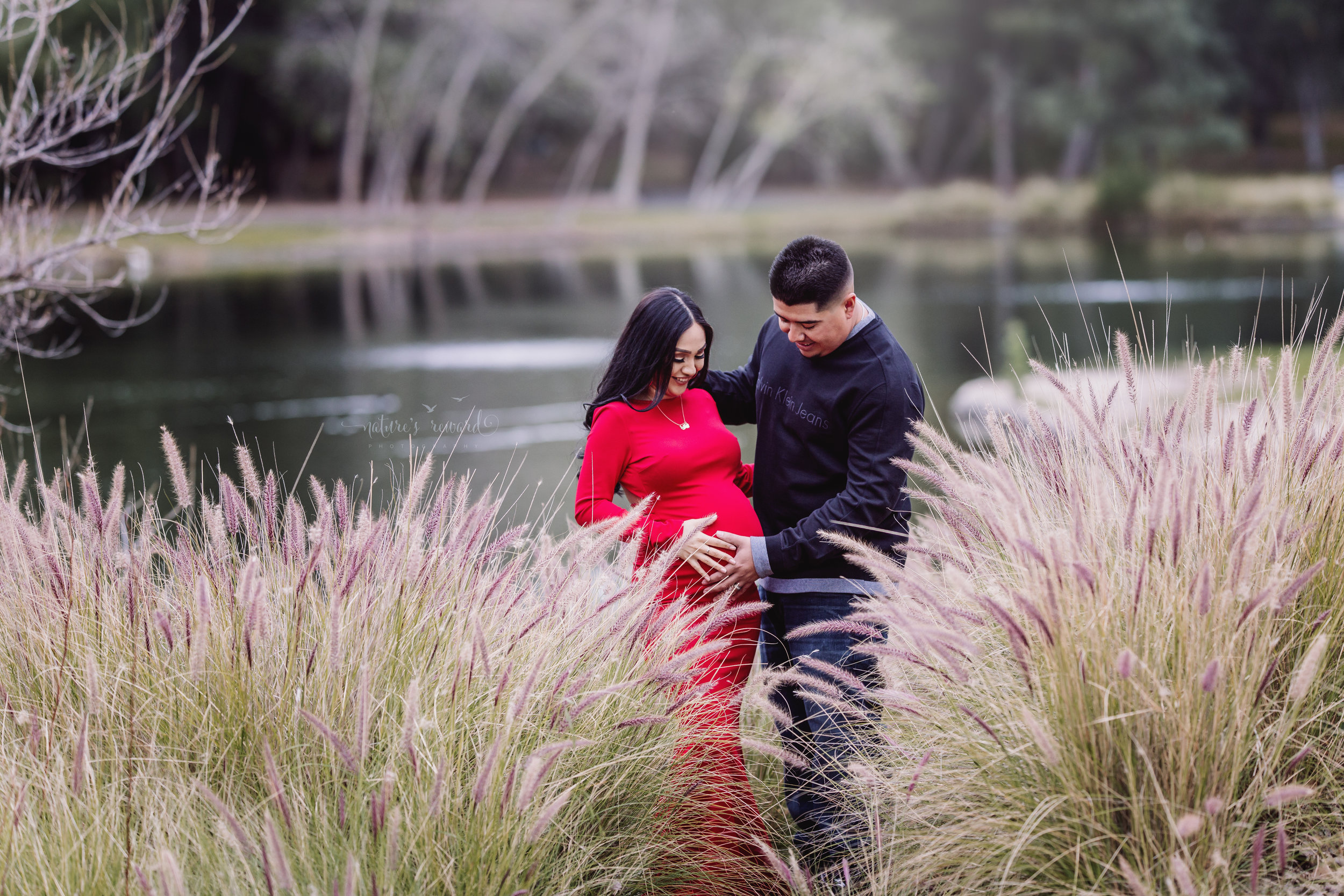 With joy and pure happiness they celebrate their baby by the water and in the long grass in this maternity portrait of mom to be in a beautiful red maternity gown and her husband in dark wash jeans and long sleeve shirt in this portrait by San Bernardino Based Photographer Nature's Reward Photography.