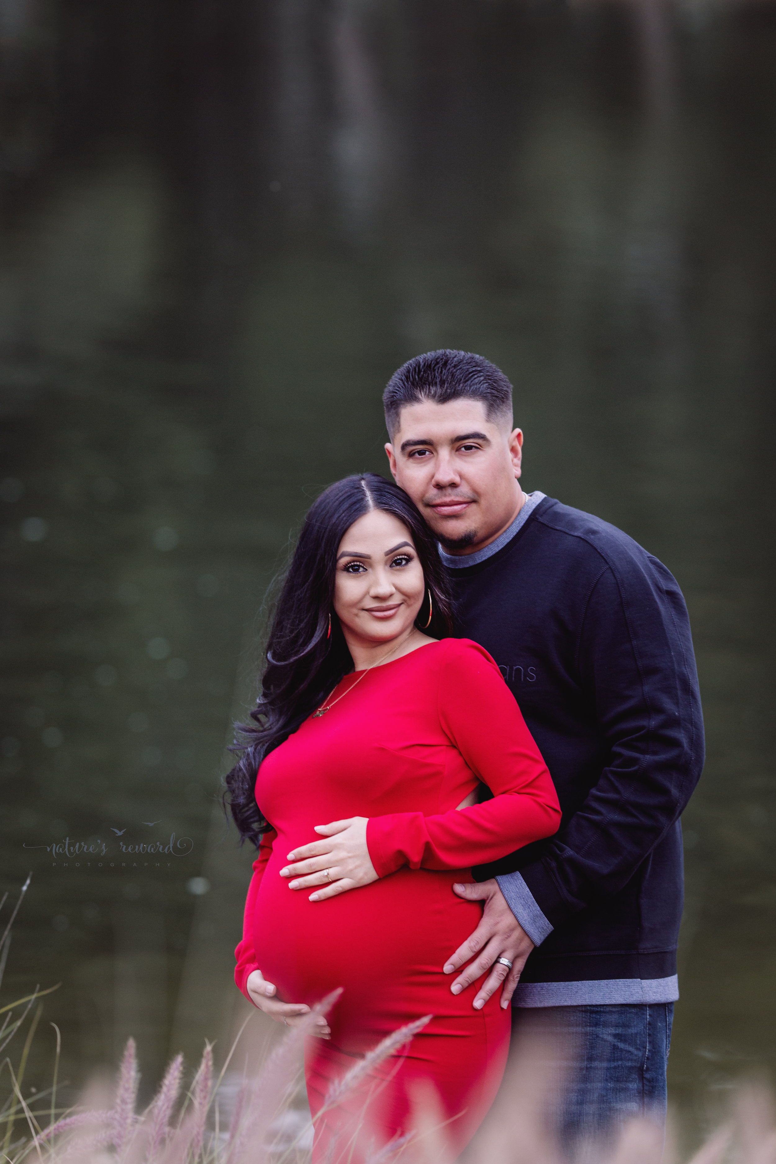 By the water maternity portrait of mom to be in a beautiful red maternity gown and her husband in dark wash jeans and long sleeve shirt in this portrait by San Bernardino Based Photographer Nature's Reward Photography.