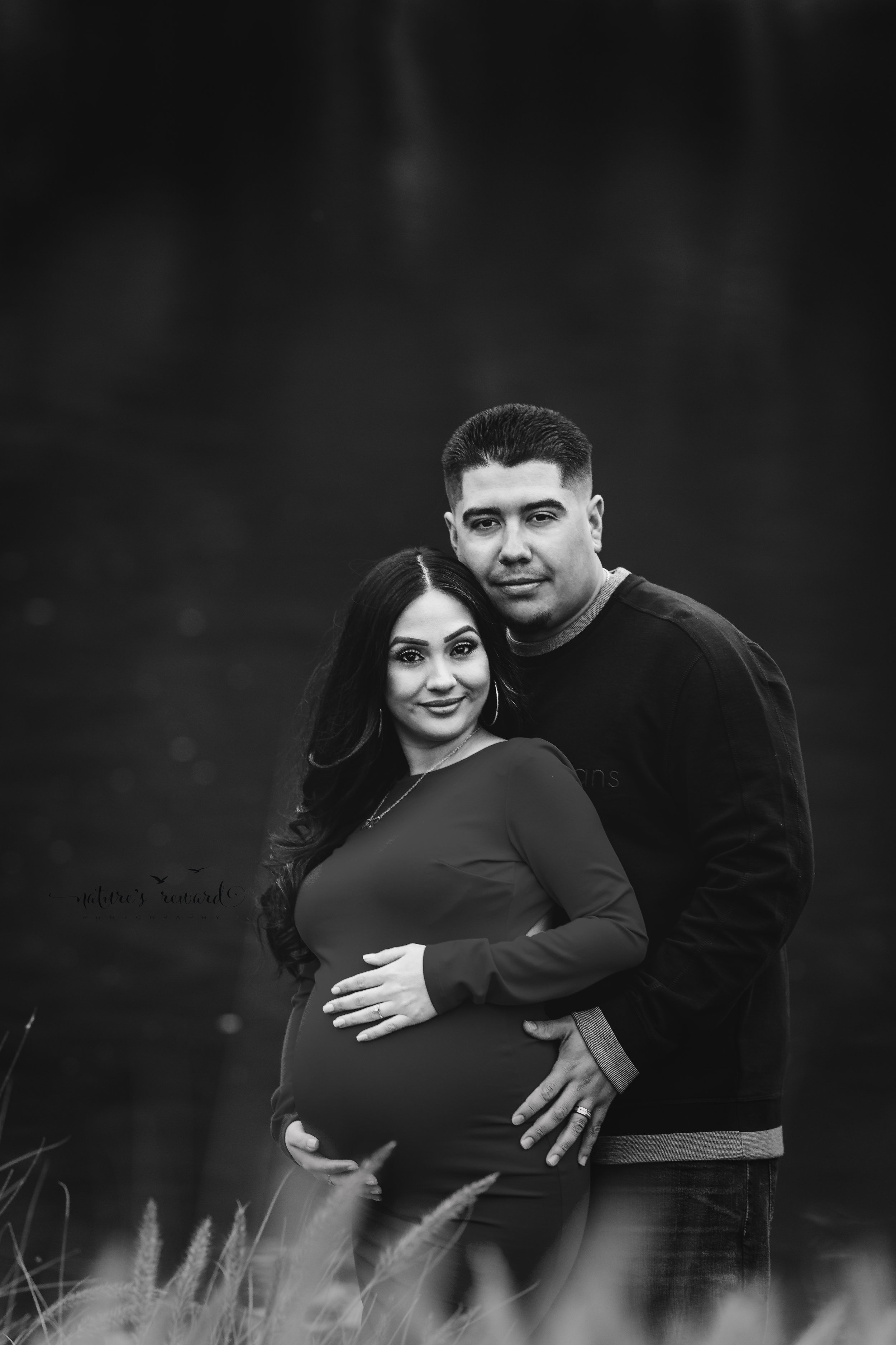 The gorgeous black and white by the water maternity portrait of mom to be in a beautiful red maternity gown and her husband in dark wash jeans and long sleeve shirt in this portrait by San Bernardino Based Photographer Nature's Reward Photography.
