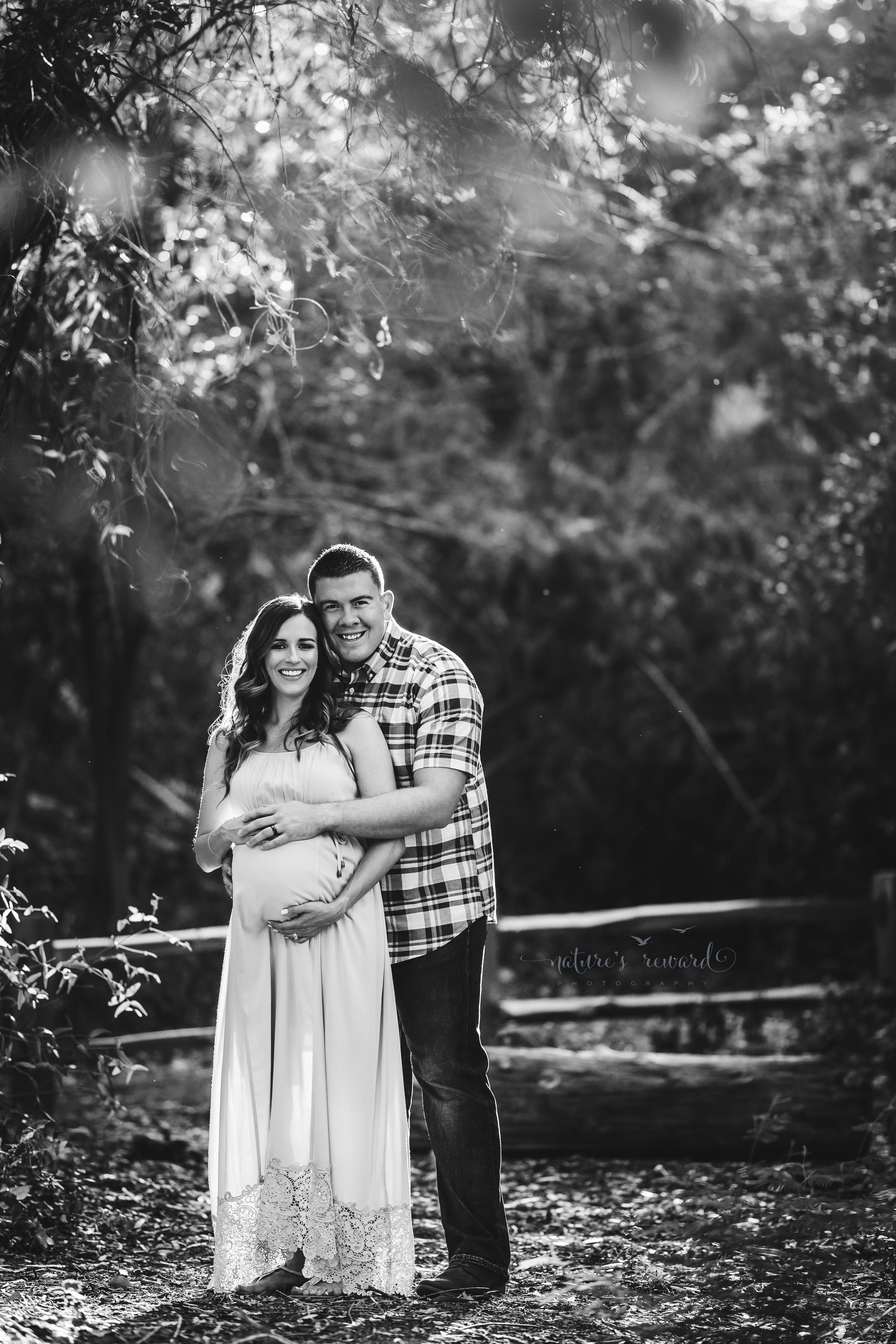 Beautiful expecting mother in a blue maternity gown with her husband in jeans and a blue plaid button down shirt in beautiful light in a park setting in this maternity black and white portrait taken by Nature's Reward Photography.