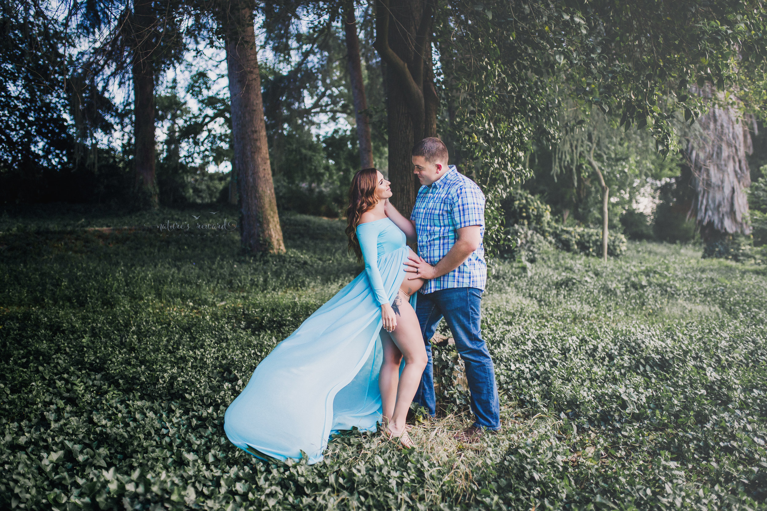 Beautiful expecting mother in a blue maternity gown with her husband in jeans and a blue plaid button down shirt in beautiful light are caught in this candid moment in a park setting in this maternity portrait taken by Nature's Reward Photography.