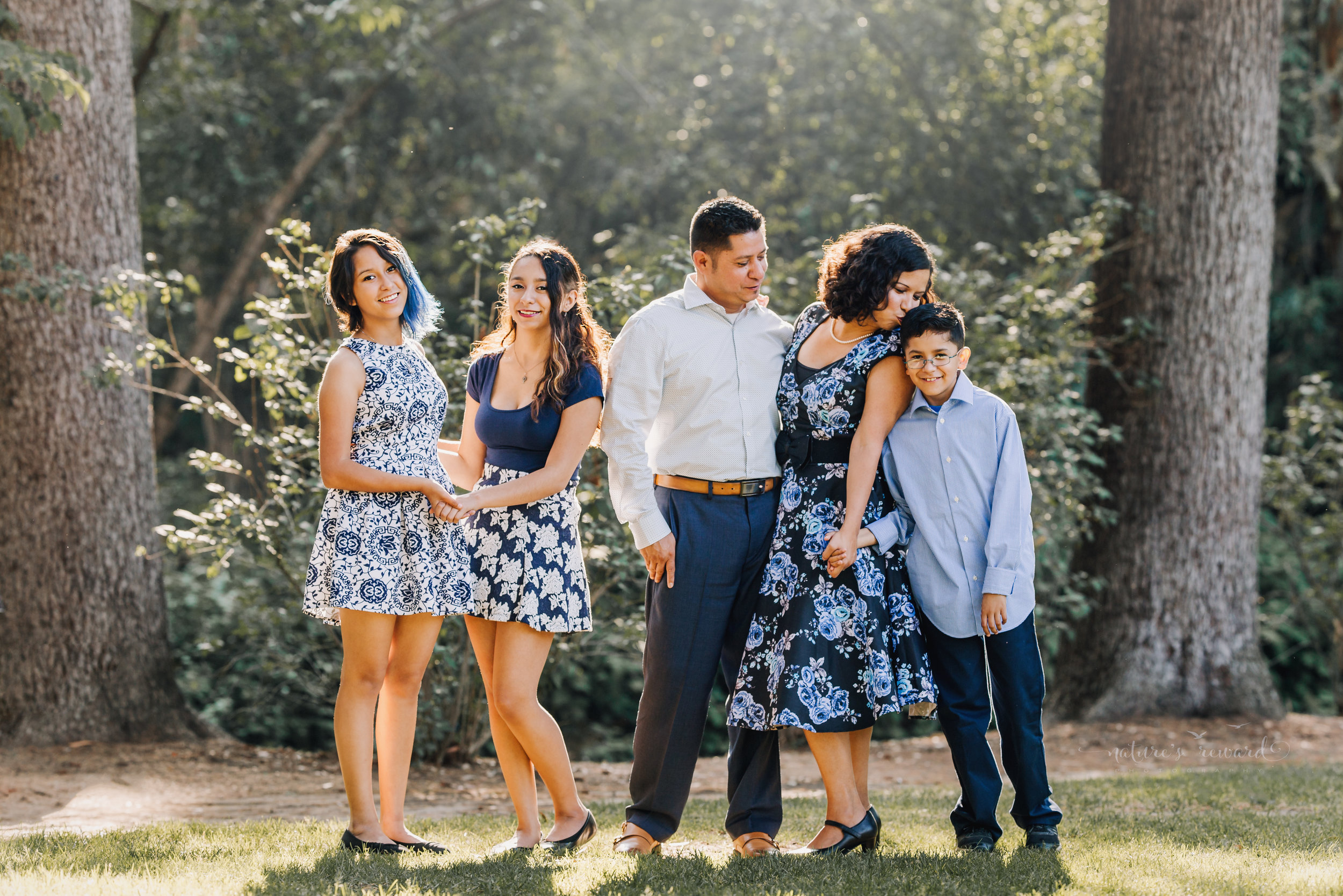 Mom kisses her beautiful baby boy.Beautiful family wearing blues and blue florals dresses in this gorgeous family photography portrait by Nature's Reward Photography.