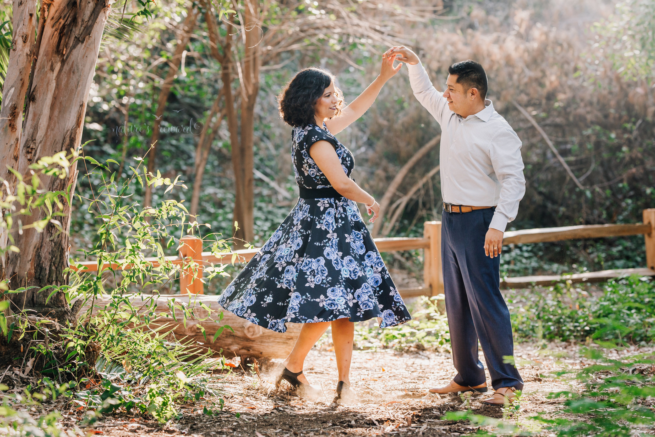 Beautiful couple wearing blues and blue floral dress dance in the park in this gorgeous family photography portrait by Nature's Reward Photography.