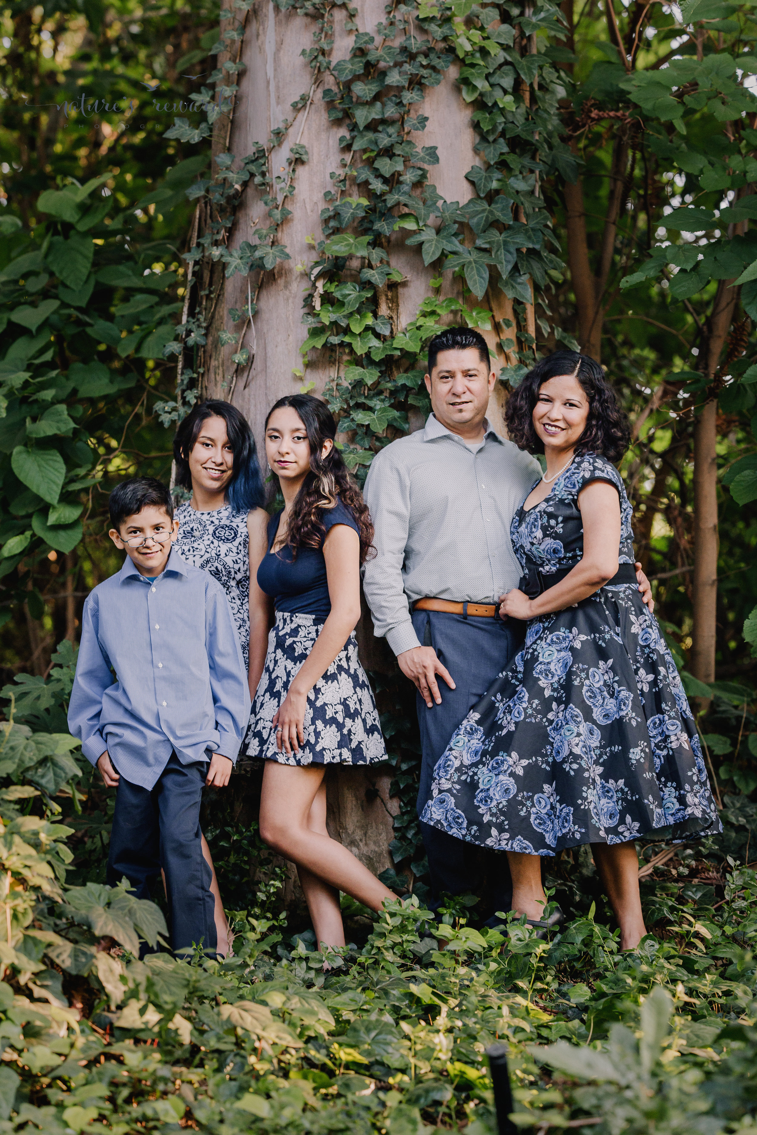 Lovely family wearing blues and blue florals dresses in this gorgeous family photography portrait by a magnificent tree with ivy by Nature's Reward Photography.