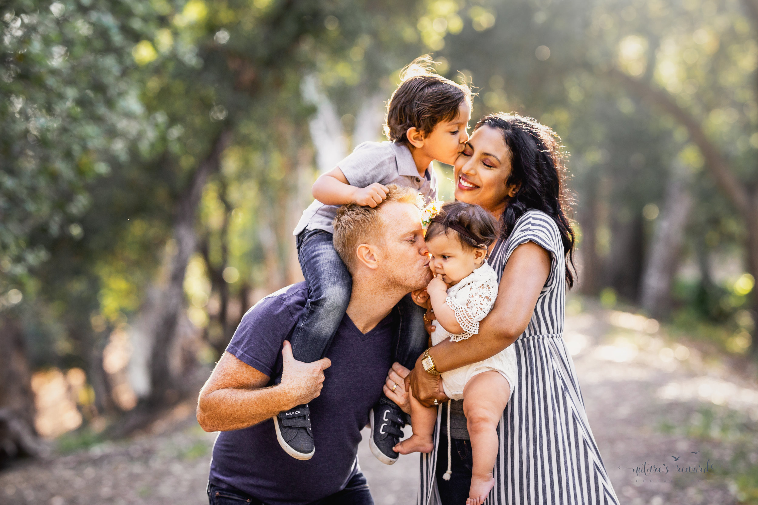 Family portrait on a tree lined dirt path by Nature's Reward Photography