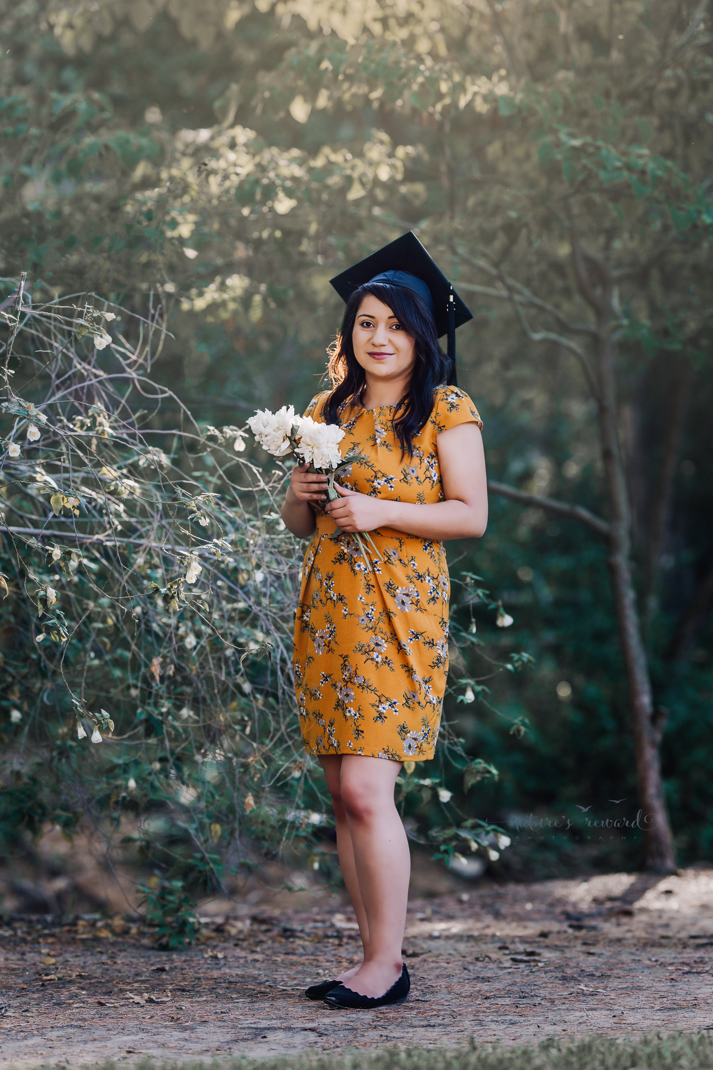 Class of 2018, California State University, San Bernardino Graduate wearing a yellow dress holding flowers surrounded by the lush green of a park in Redlands, California in this Senior Portrait by Nature's Reward Photography.
