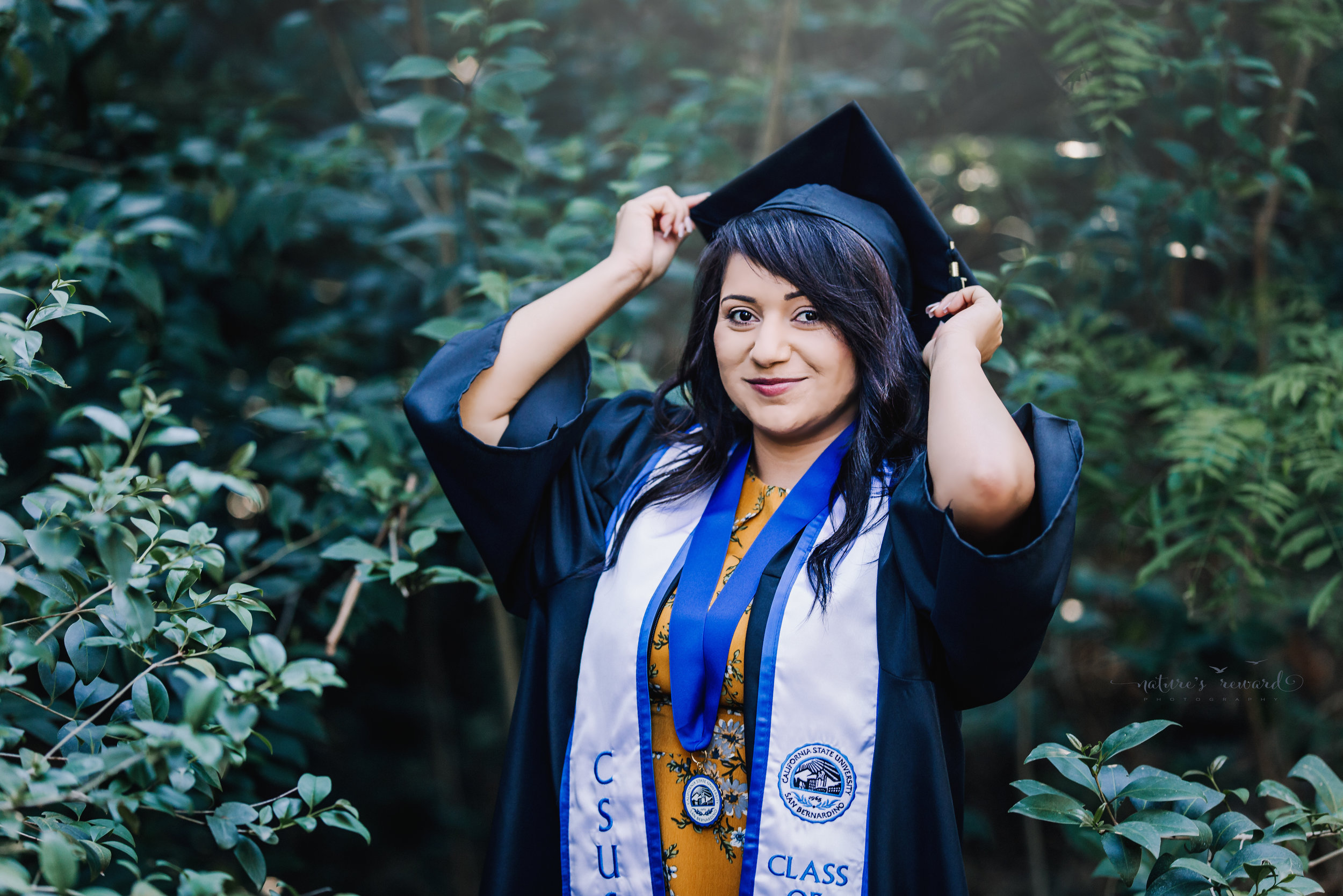 Class of 2018, California State University, San Bernardino Graduate wearing a yellow dress and cap and gown surrounded by the lush green of a park in Redlands, California in this Senior Portrait by Nature's Reward Photography.