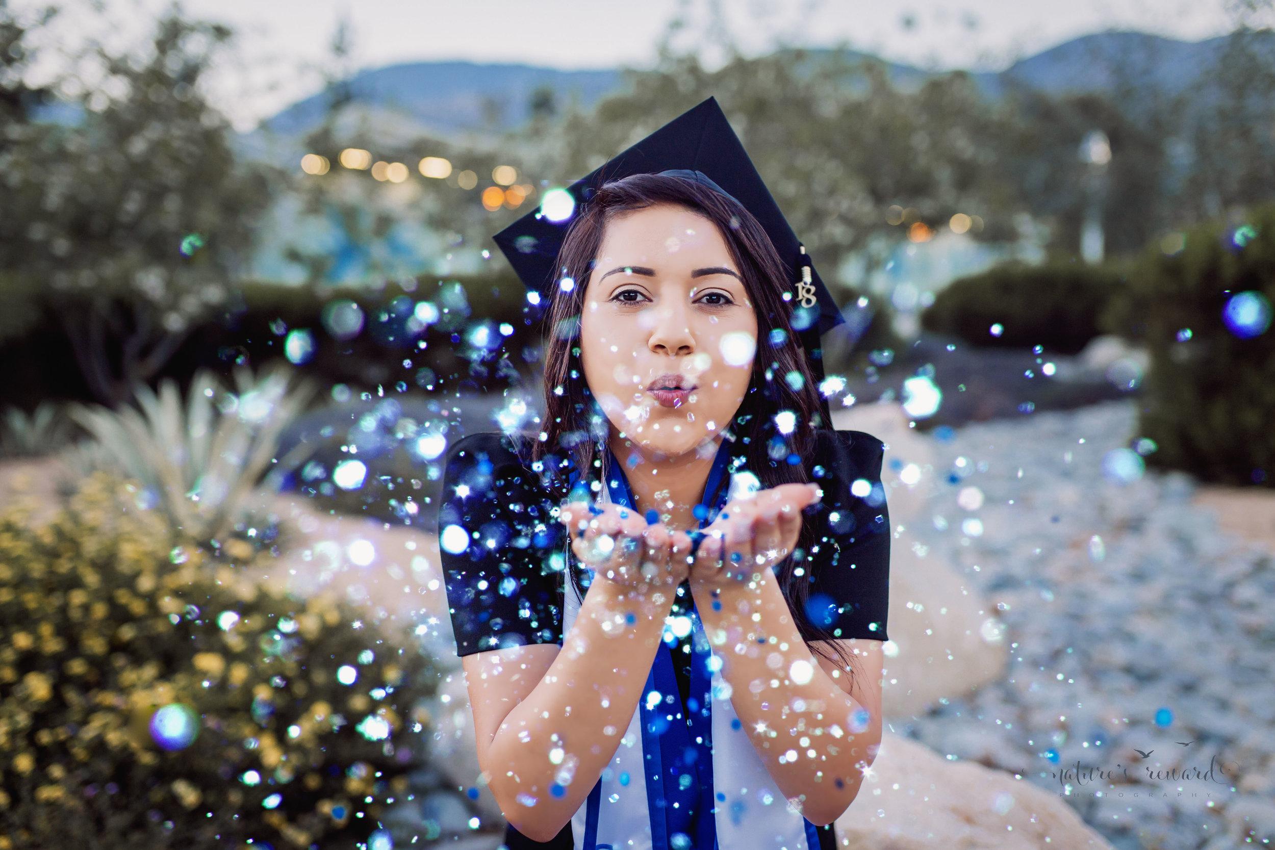 Class of 2018, California State University, San Bernardino Graduate wearing a black dress and Cap blowing celebratory glitter, in this Senior Portrait by Nature's Reward Photography.