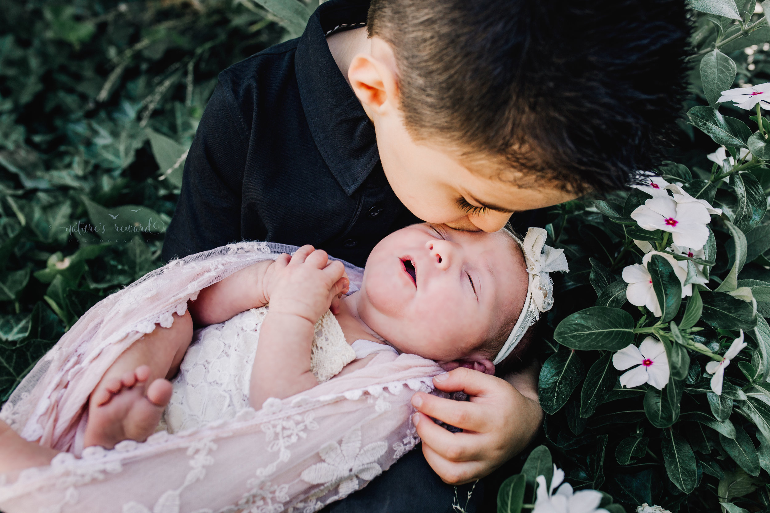 Newborn Baby Girl in a lace romper swaddled in pink lace in a garden with white flowers being held by her big brother. A Portrait By Nature's Reward Photography, a San Bernardino Family, Child, and Newborn Baby Photographer.