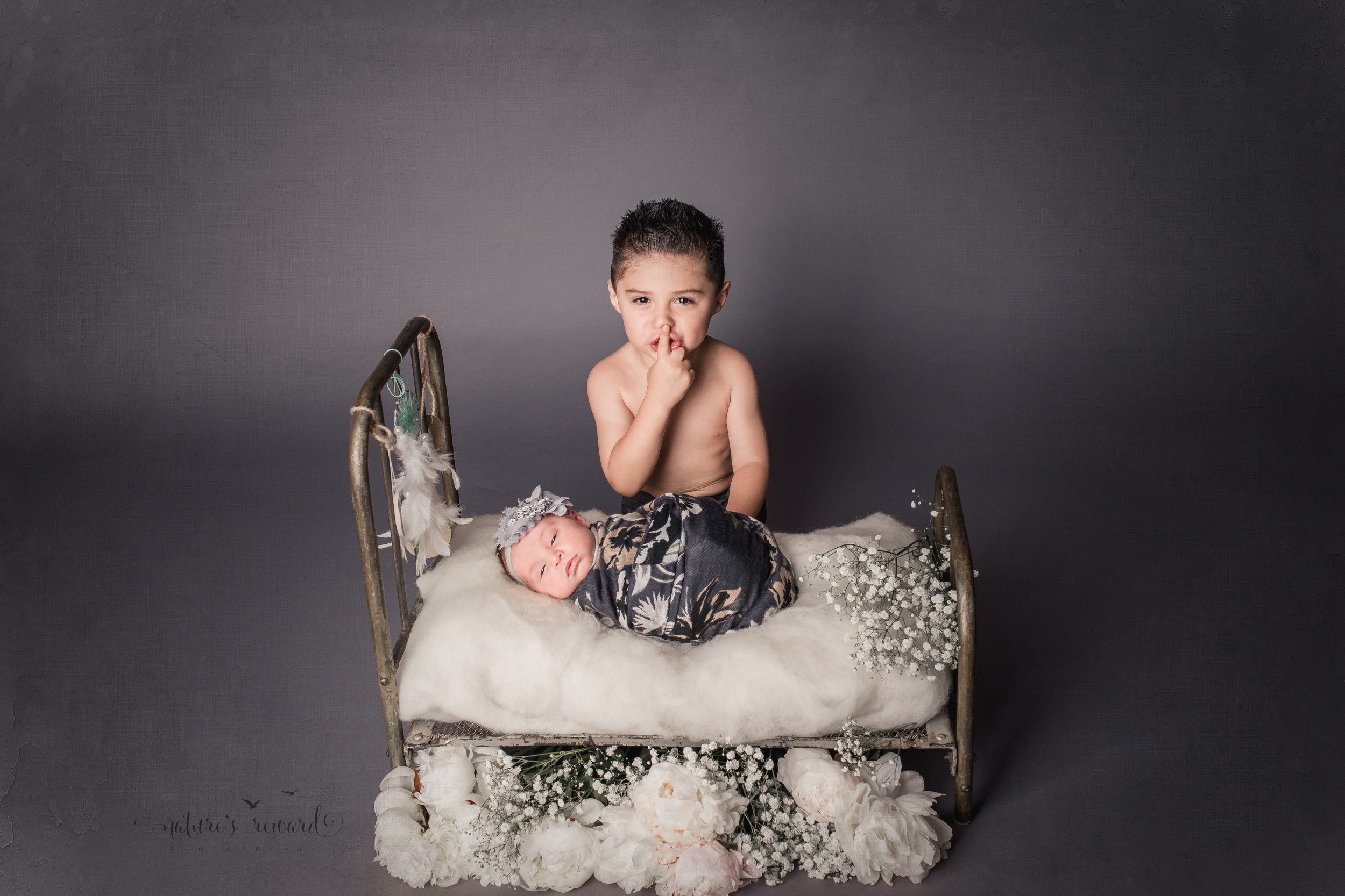 Sibling newborn baby portrait in greys and whites, laying on a doll bed.A Portrait By Nature's Reward Photography, a San Bernardino Family, Child, and Newborn Baby Photographer.